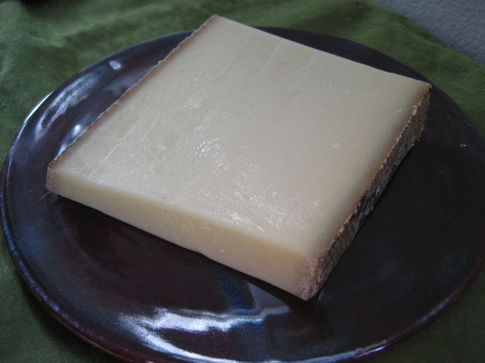 Slice of Alpine cheese (mountain cheese) on a plate