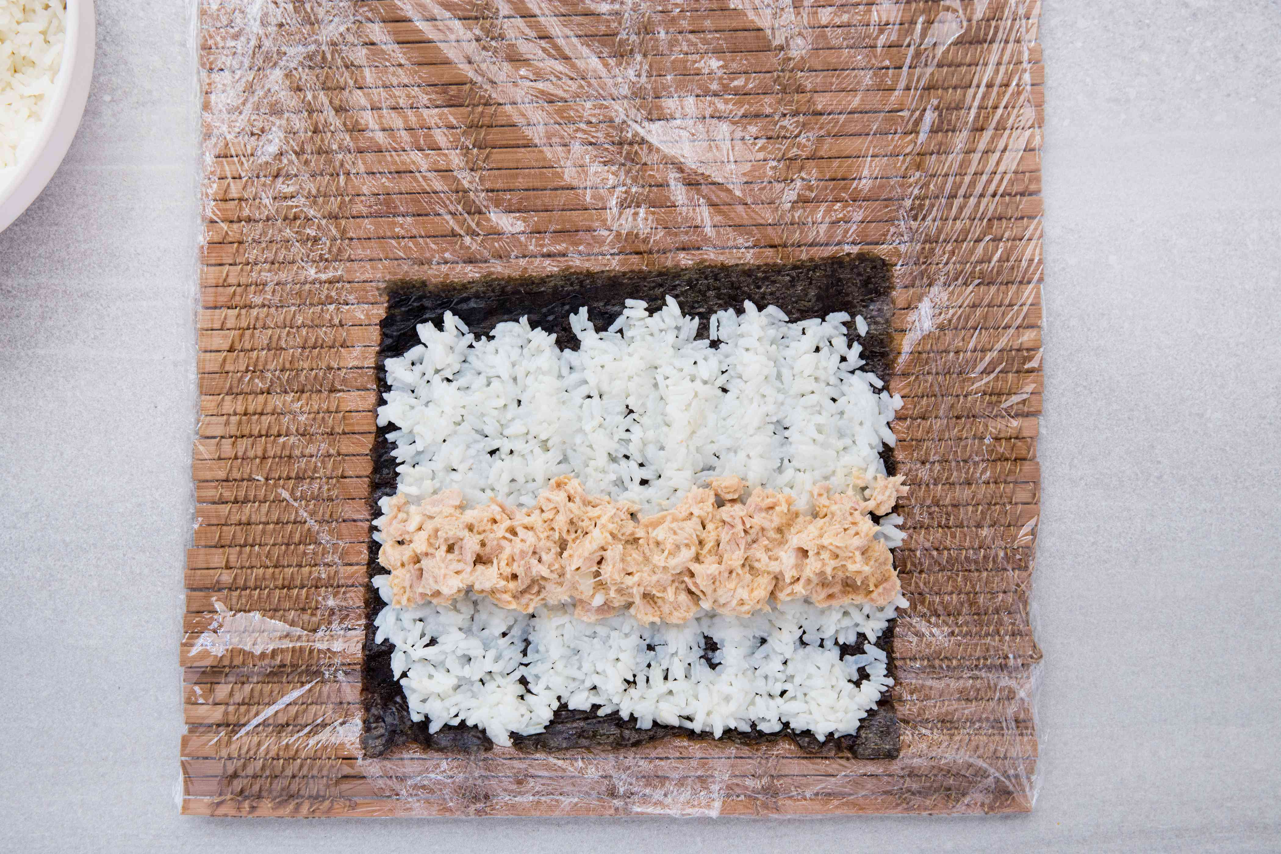 bamboo mat with plastic wrap, with seaweed, rice and tuna salad on top