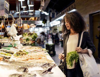 Woman examining fish in market