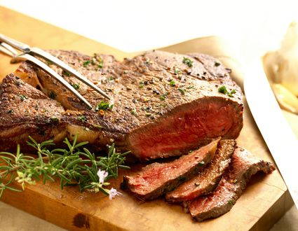 Sliced London broil on a carving board