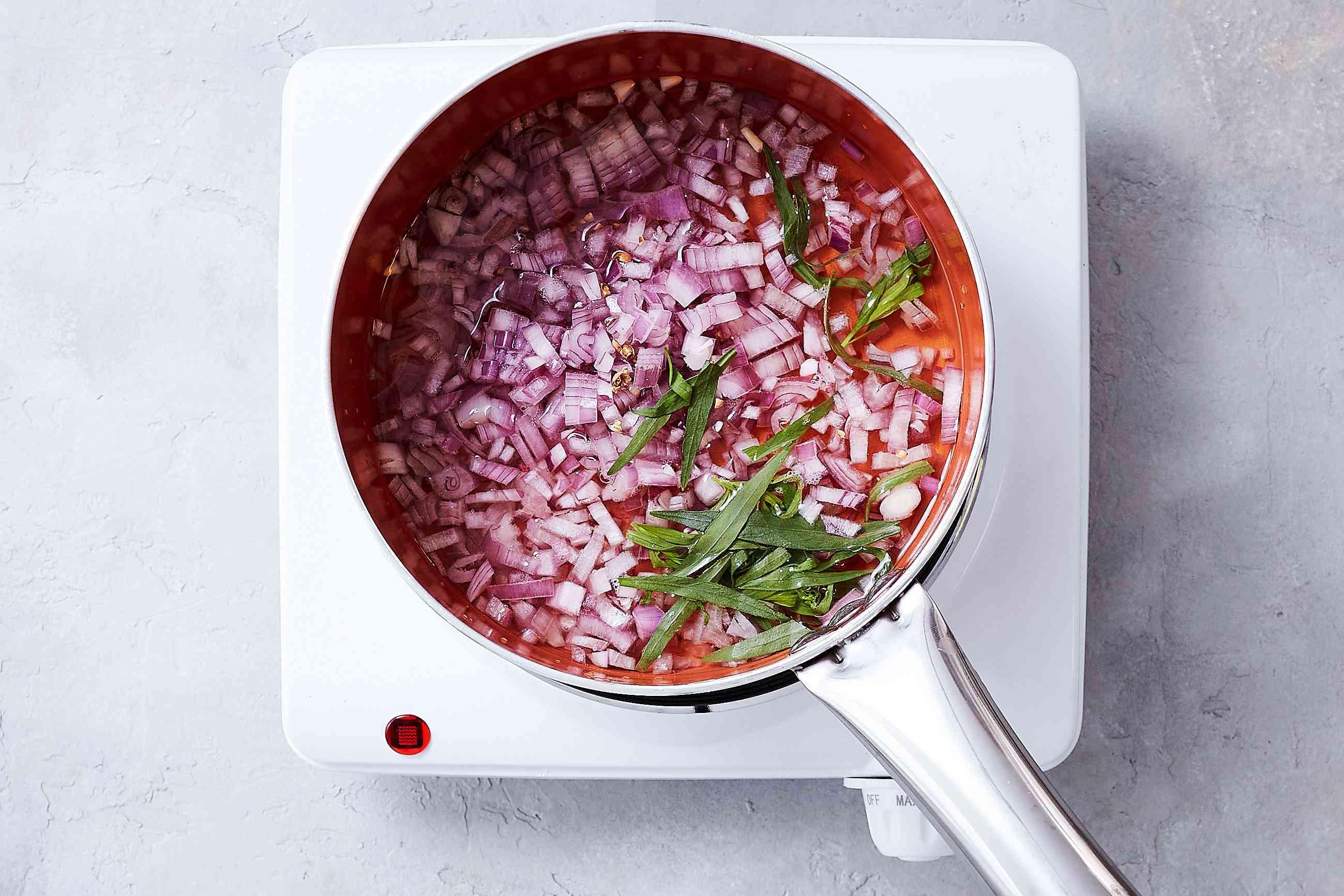 Vinegar, wine, shallots, tarragon, and peppercorns in a saucepan