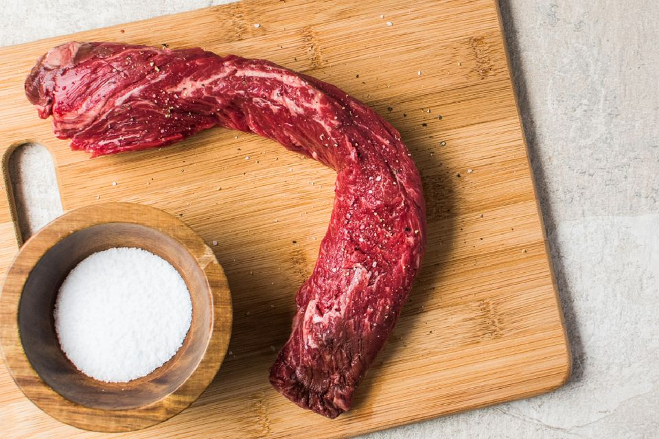 hanger steak on wooden cutting board