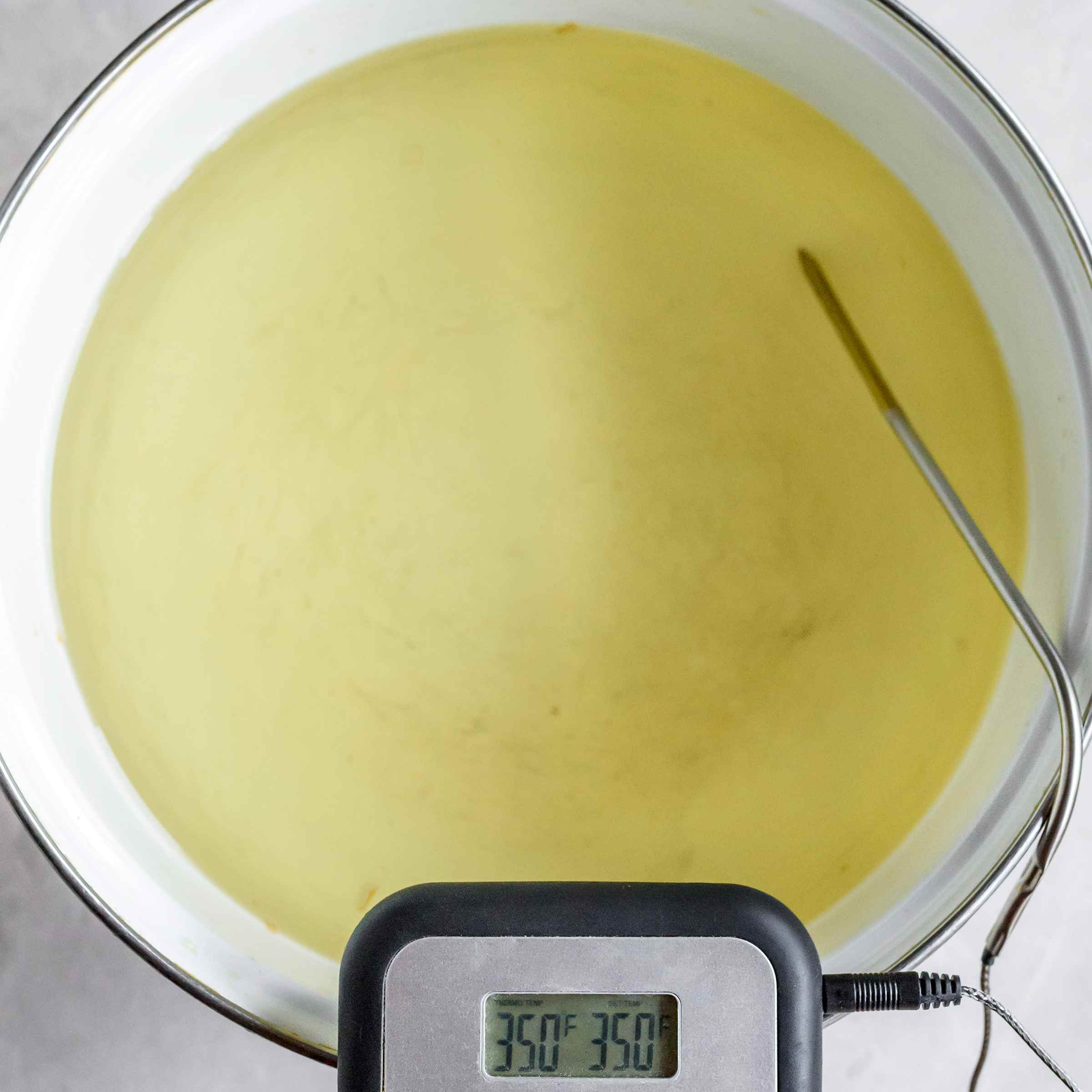 Heated oil in bowl with thermometer reading 350 F