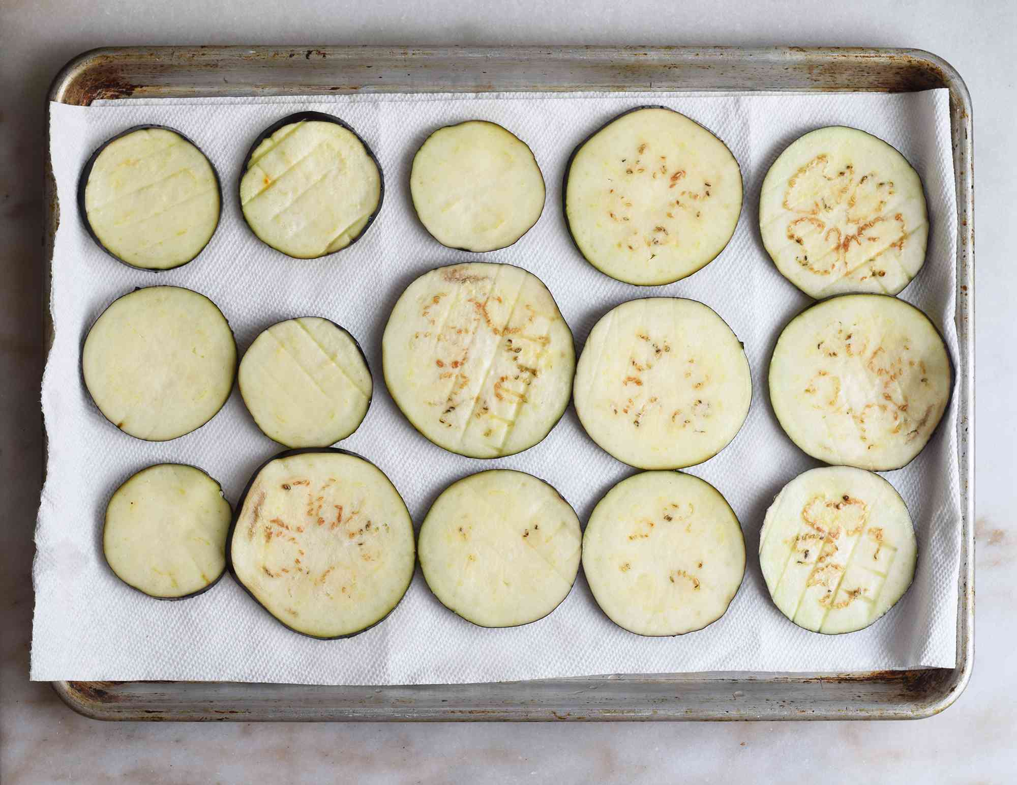 eggplant slices drying on a baking sheet