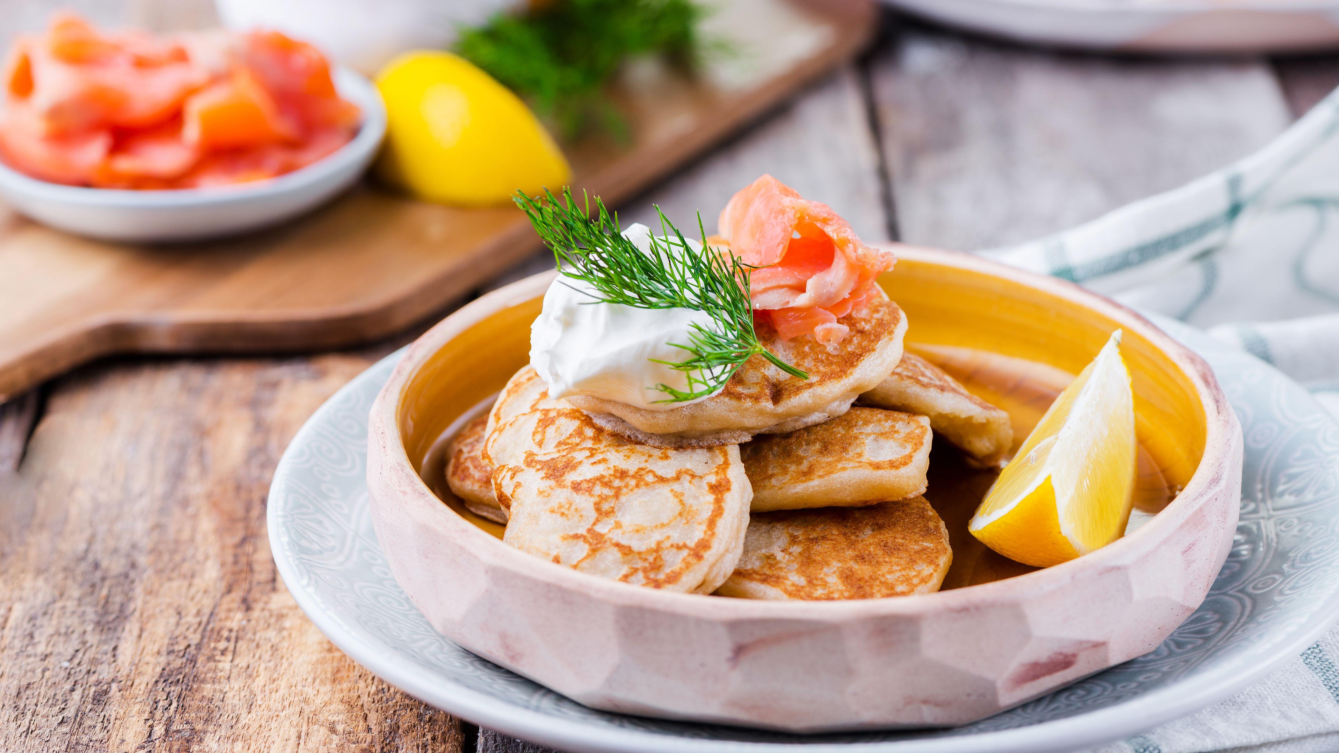 bánh blini trong đĩa trên bàn, miếng canh vàng trong bát