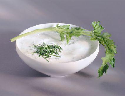 Yogurt in bowl with leaf, close-up