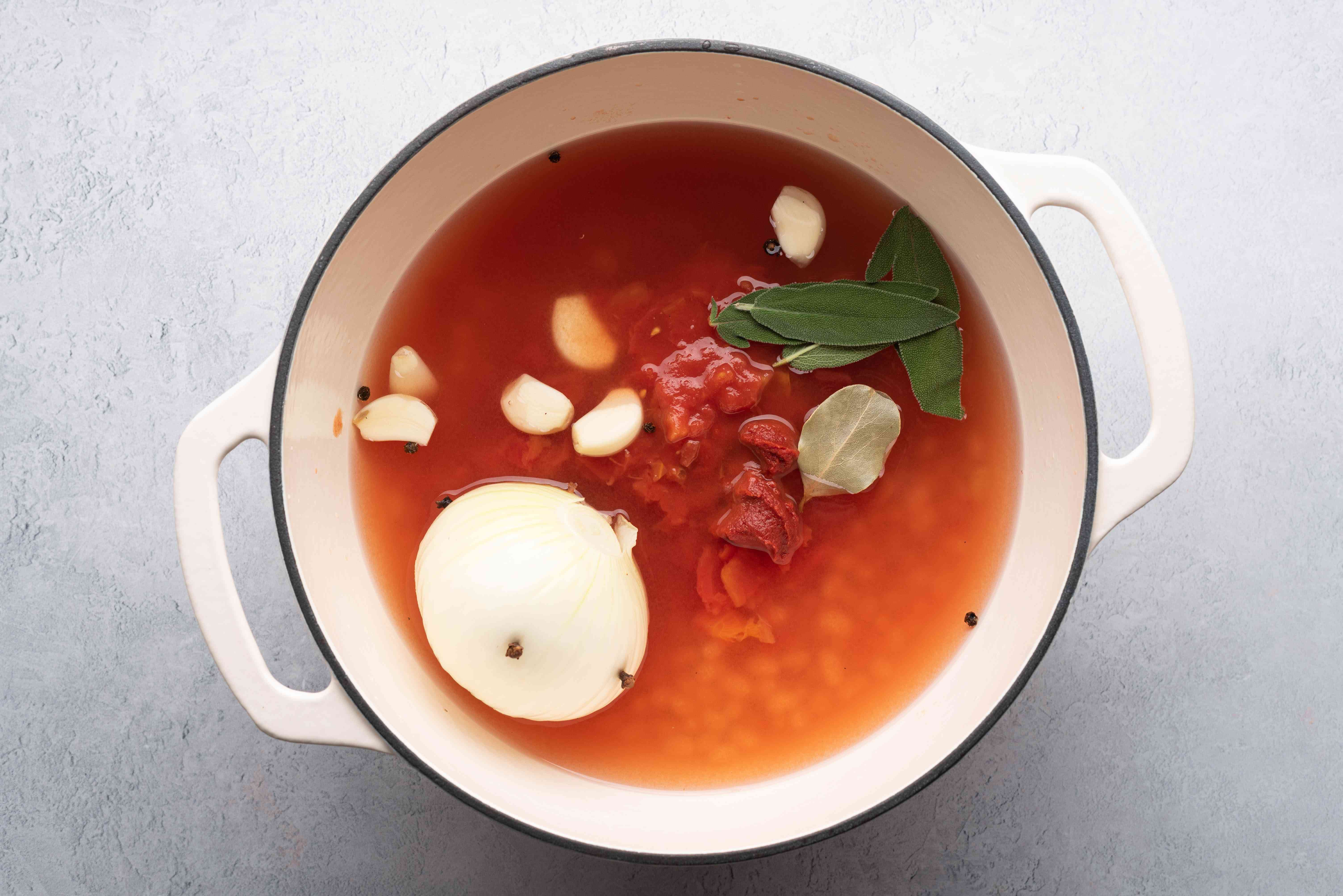tomato concentrate, black peppercorns, bay leaf, sage, garlic, and canned tomatoes in a pot with the beans