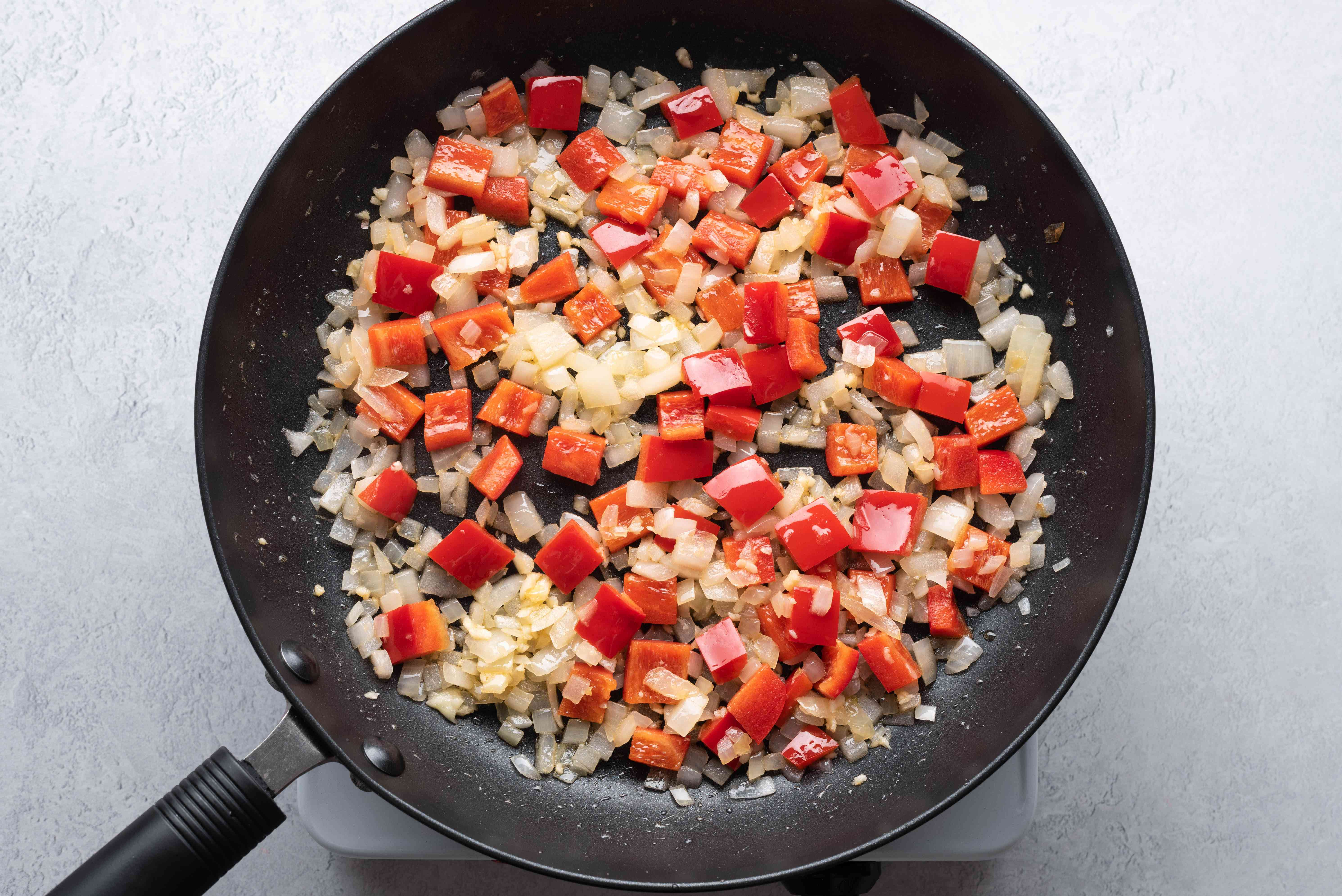garlic, red pepper and onions cooking in a pan