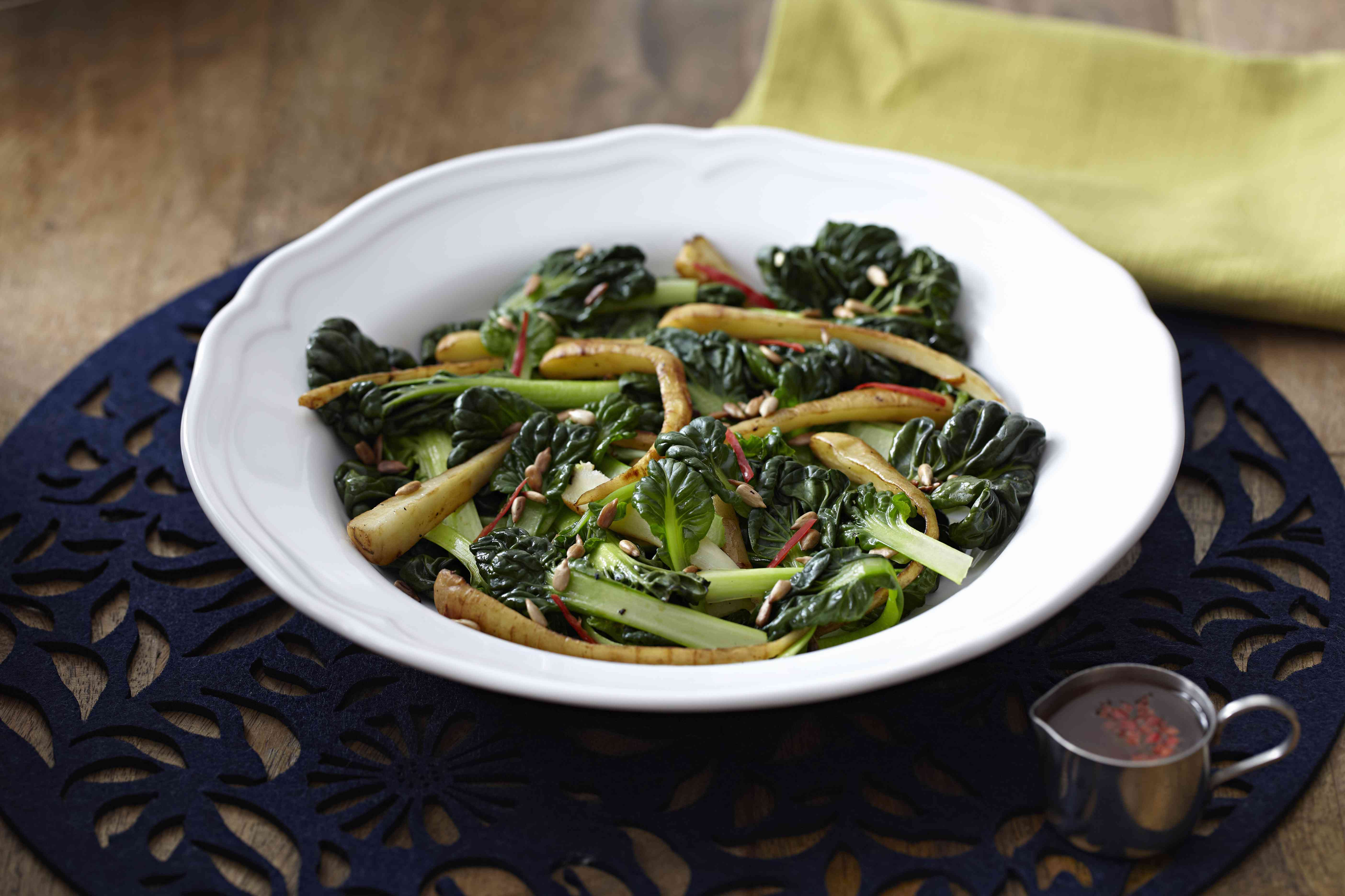 Chard and parsnip salad with pine nuts in bowl