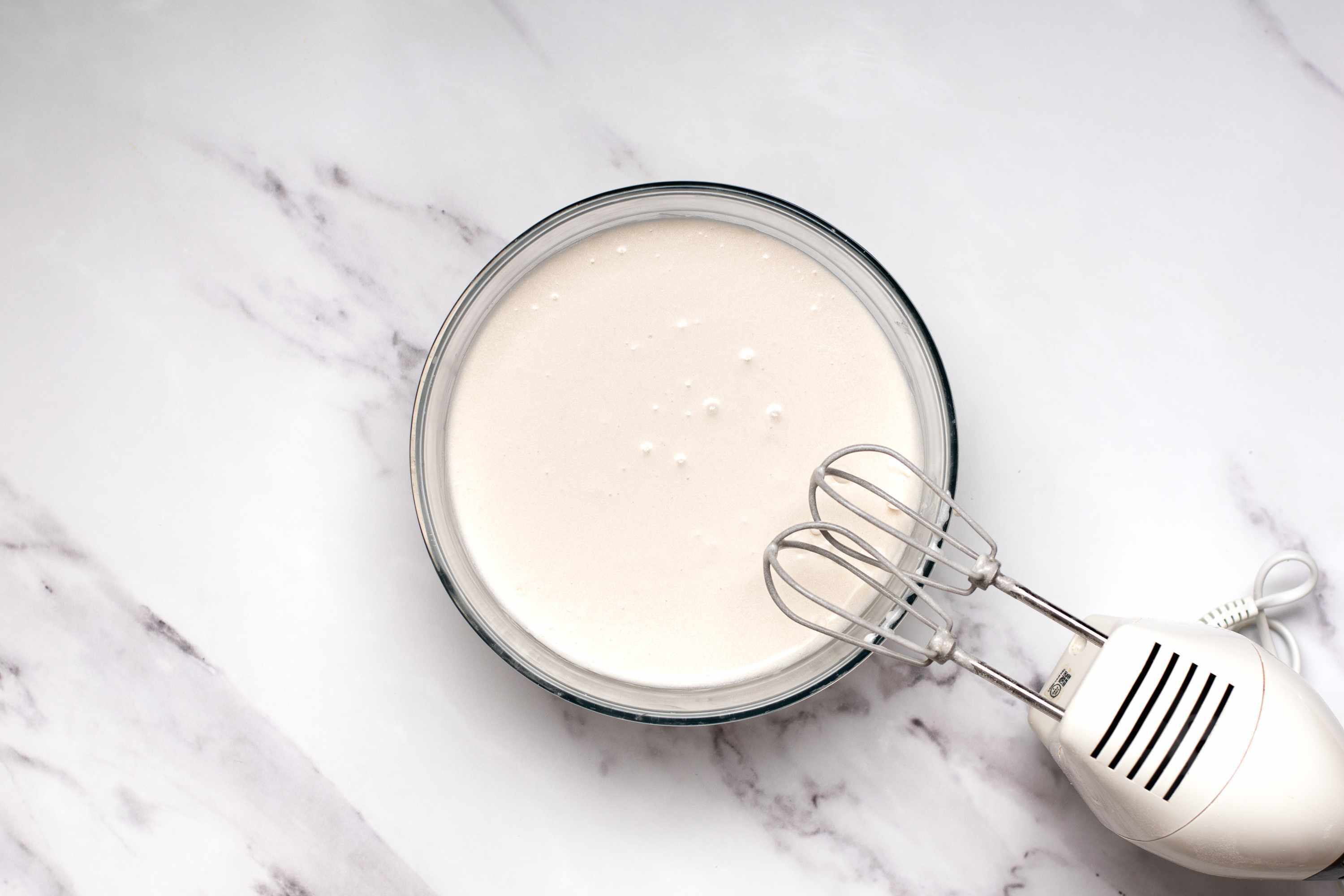 coconut milk mixture with flour and baking powder in a bowl, hand mixer