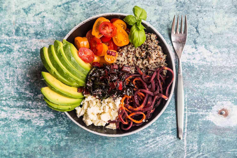 Lunch bowl of quinoa tricolore, chard, avocado, carrot spaghetti, tomatoes and feta