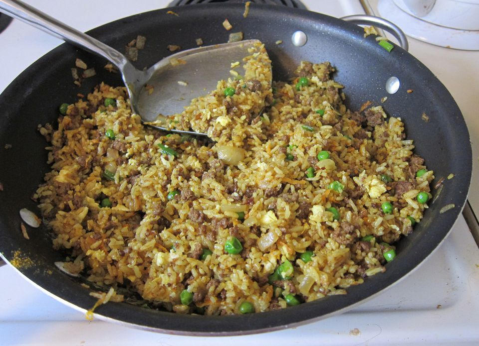 Ground beef fried rice with curry powder in a black skillet