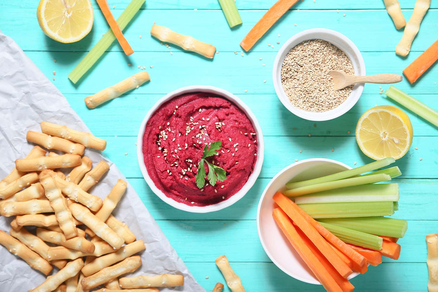 Bowl of beetroot hummus, sesame, carrot and celery crudités and breadsticks