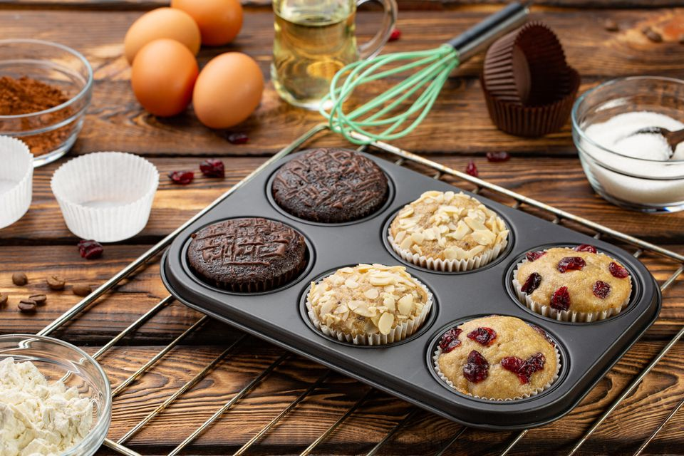 Different Muffins in bakeware or muffin pan on broun wooden background. Basic muffin recipe. Homemade muffins for breakfast or dessert.