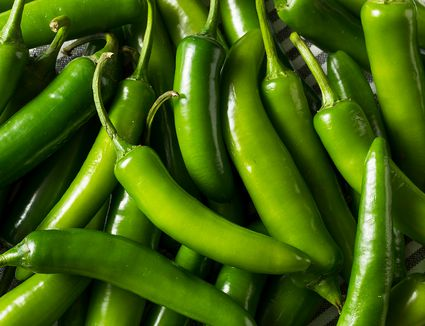 Raw green organic serrano peppers
