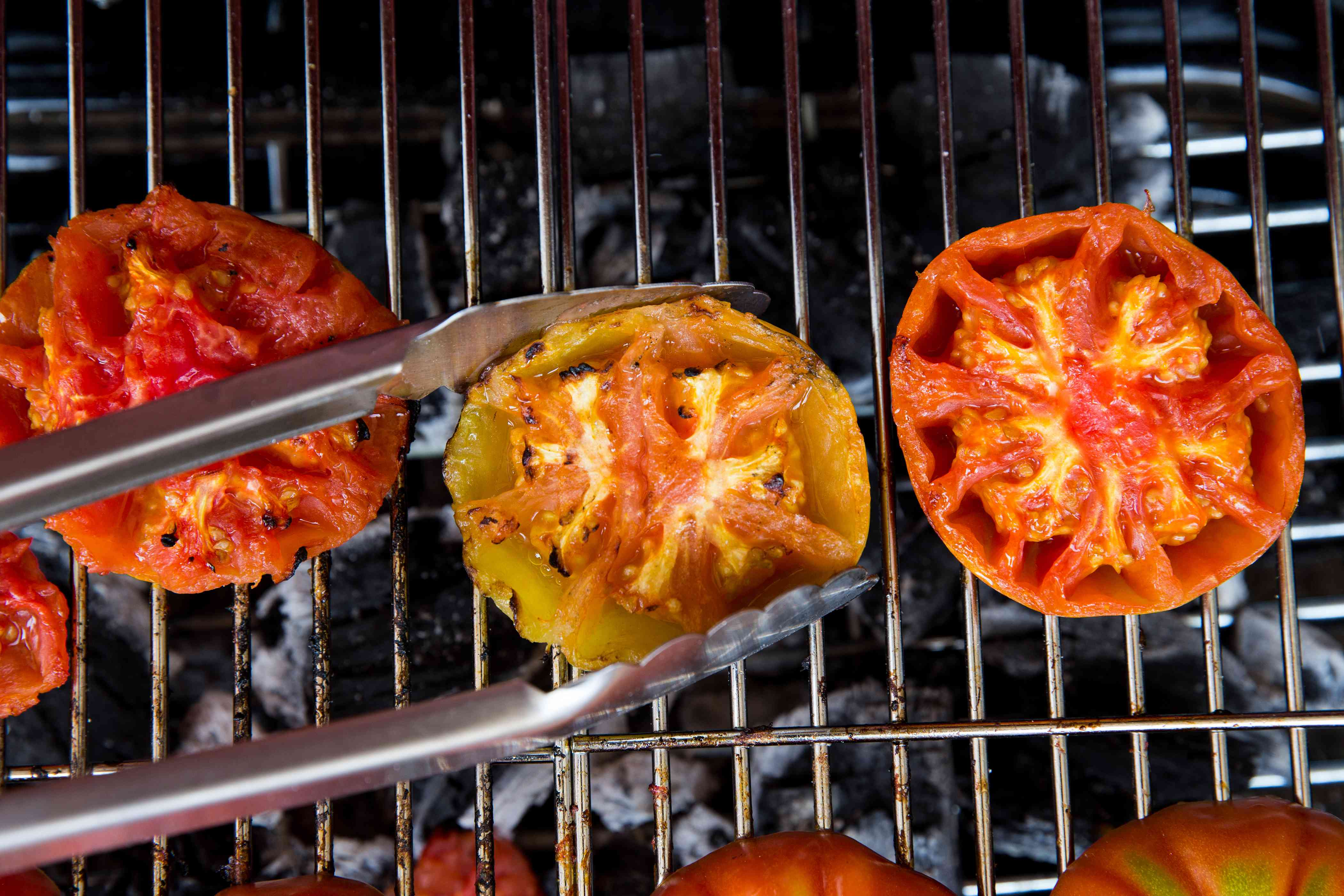 Removing cooked tomatoes from the grill