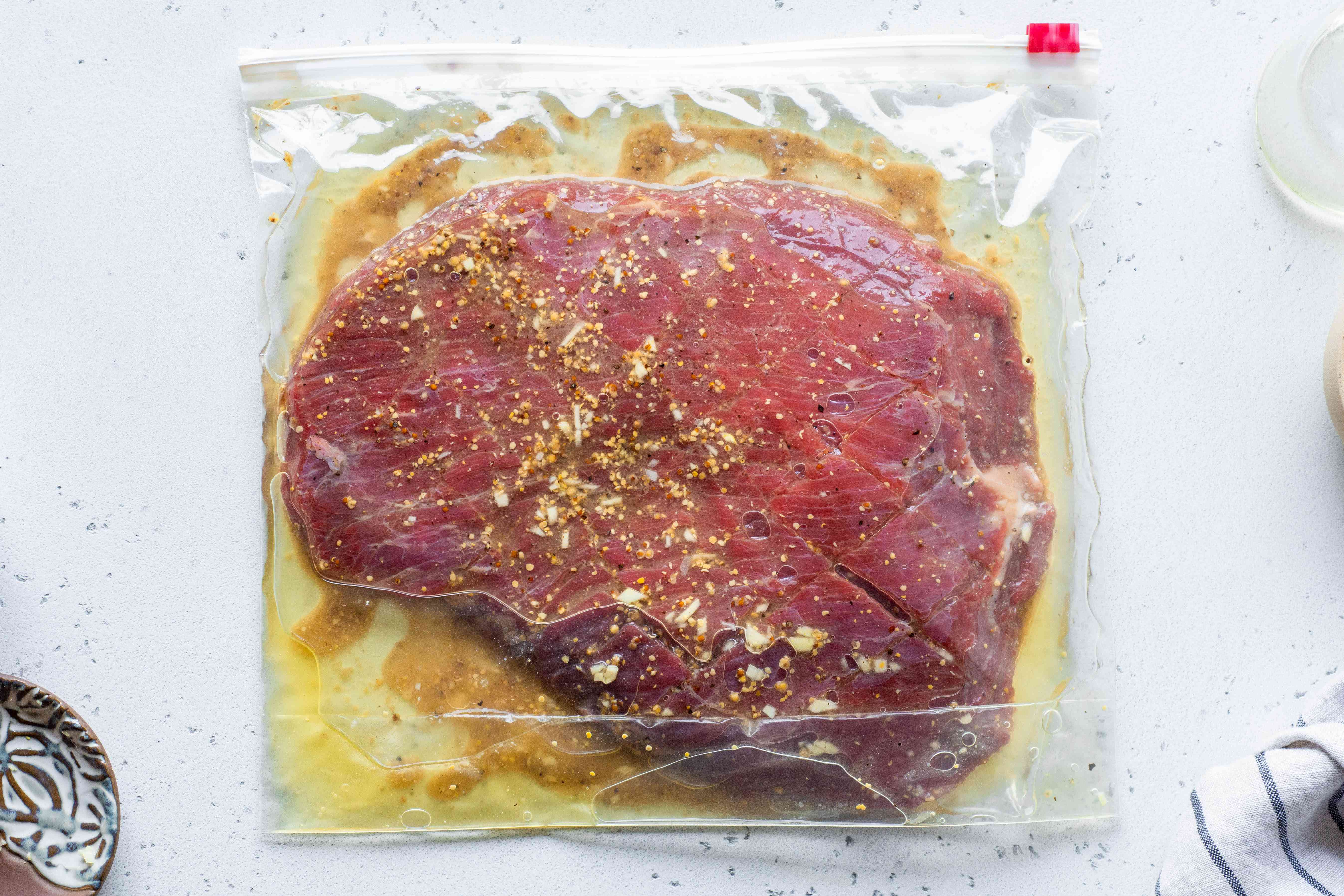 flank steak in a plastic bag with marinade