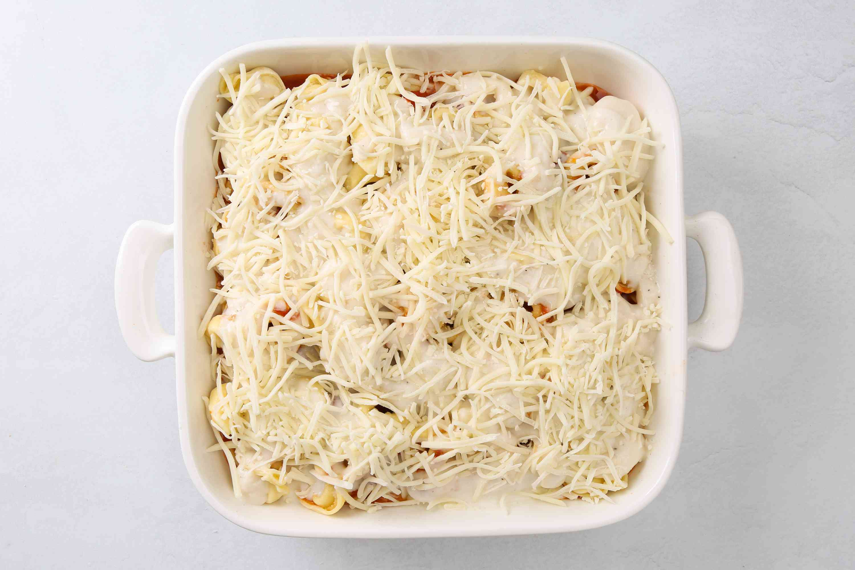 cheese on top of the Alfredo sauce in the baking dish