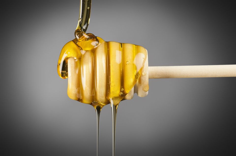 Honey drizzling off of a honey dipper