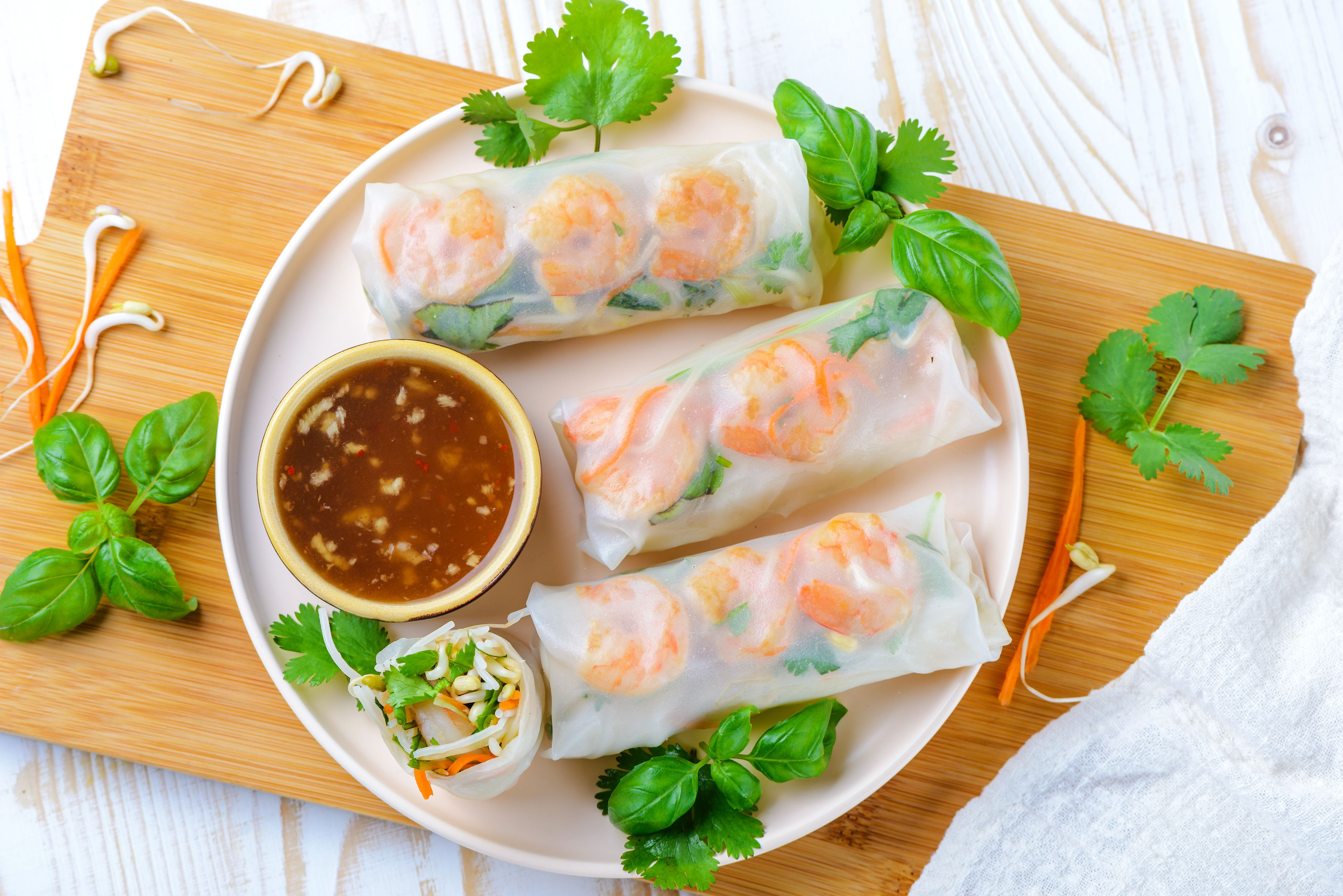 Thai fresh spring rolls with dipping sauce on a cutting board, garnished with Thai basil and cilantro