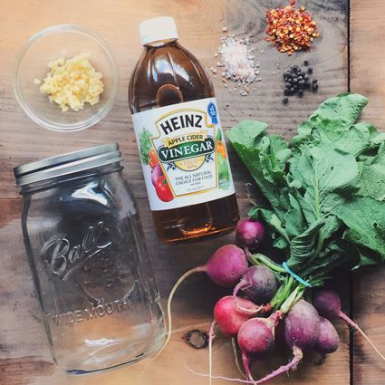 Bottle of vinegar, radishes, Mason jar and other ingredients