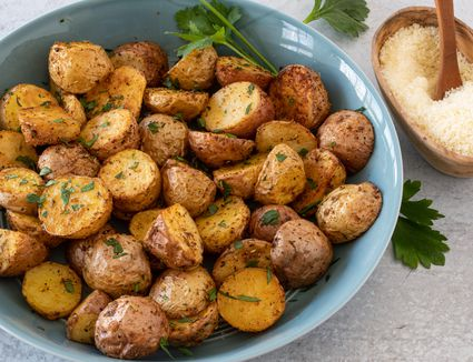 air fryer potatoes with parsley garnish and parmesan cheese on the side