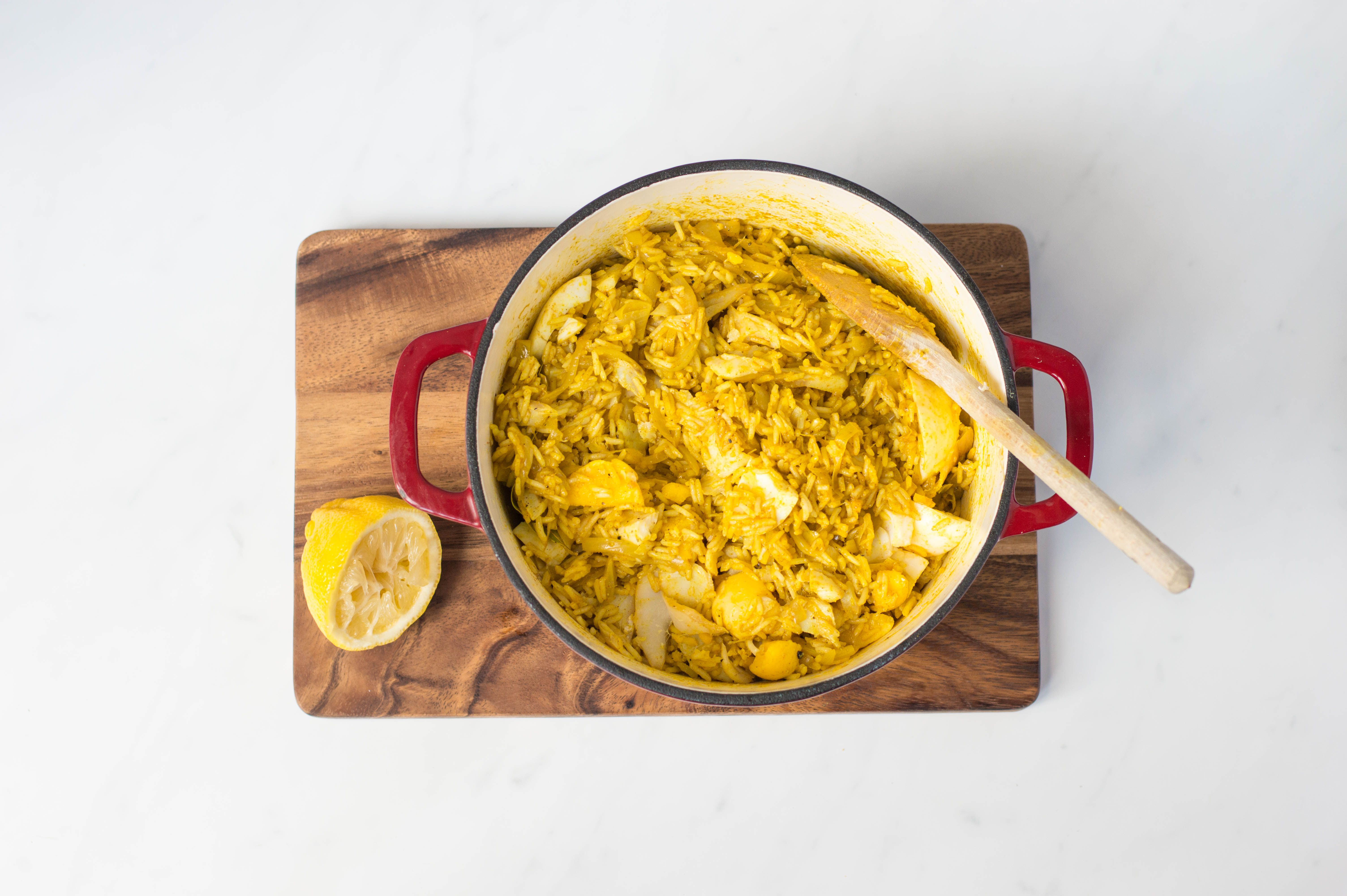 Lemon juice added to kedgeree in a pan