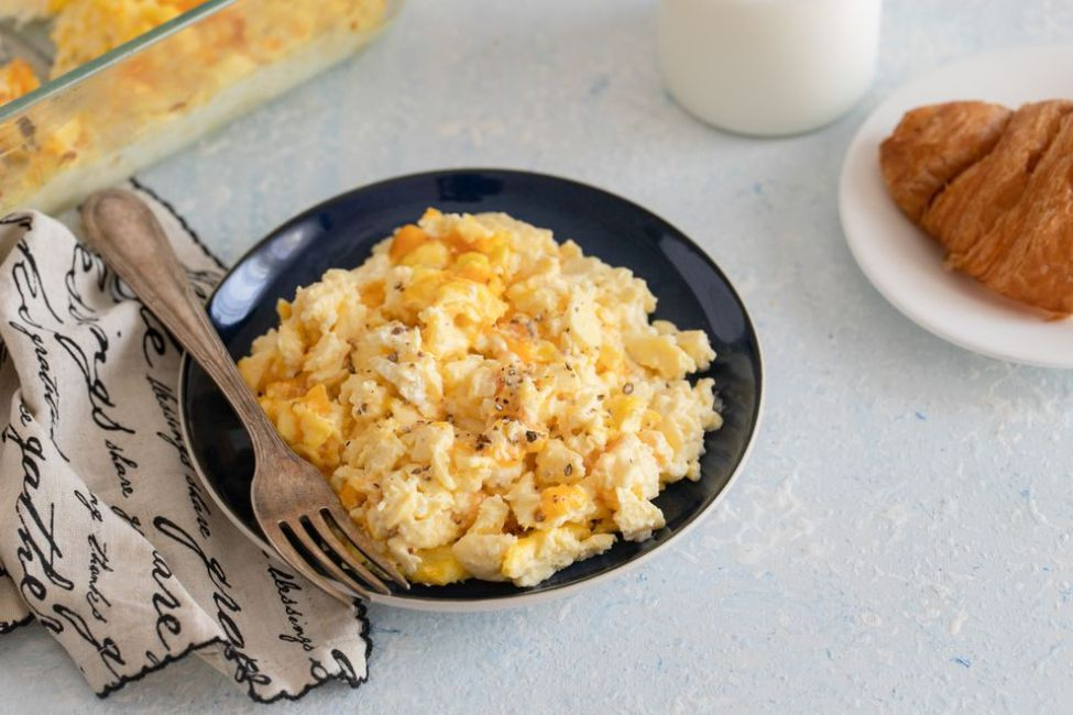 Make-ahead cheesy scrambled eggs on a plate with a fork