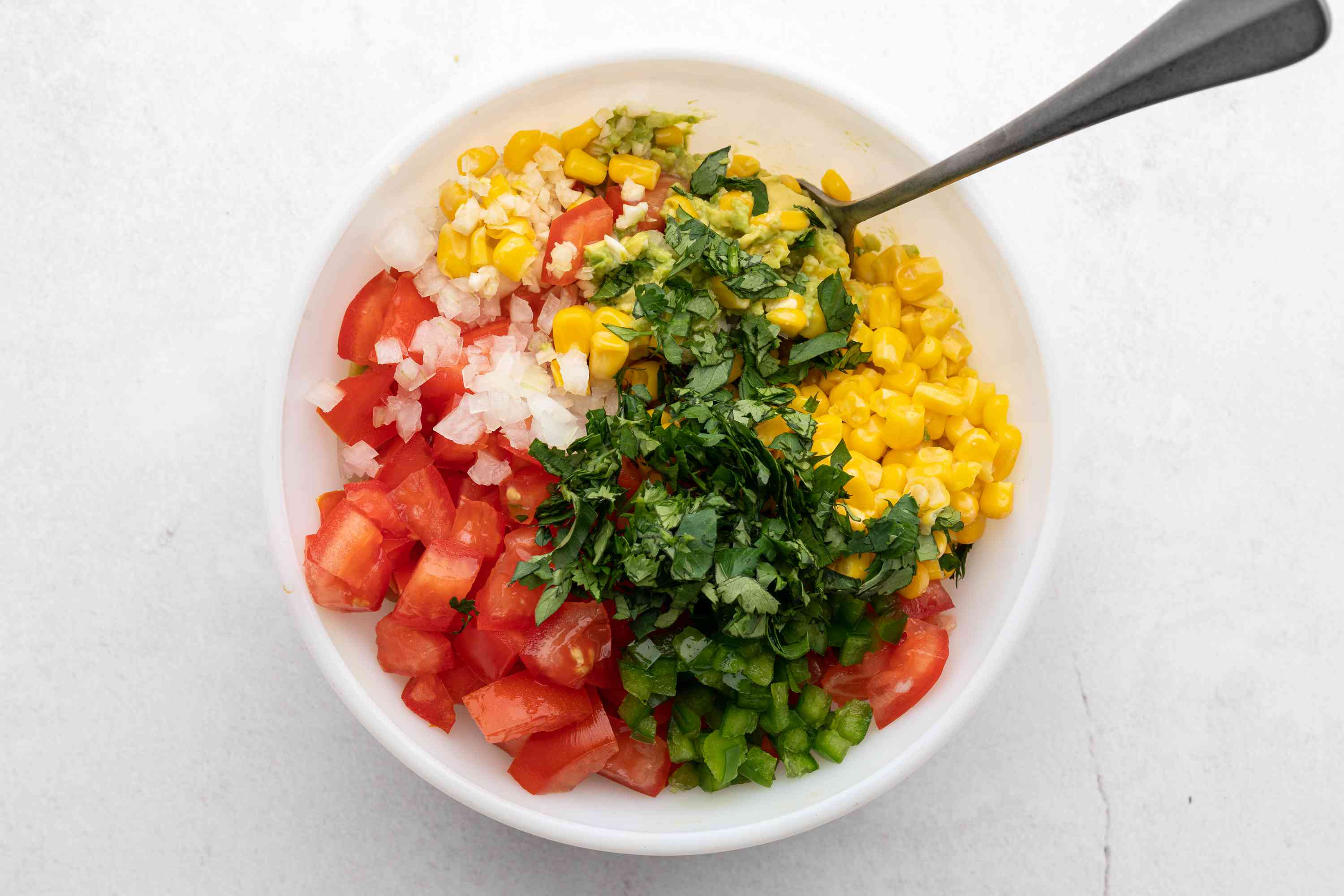 tomatoes, jalapeño, onion, garlic, cilantro, corn, and lime in a bowl with mashed avocados
