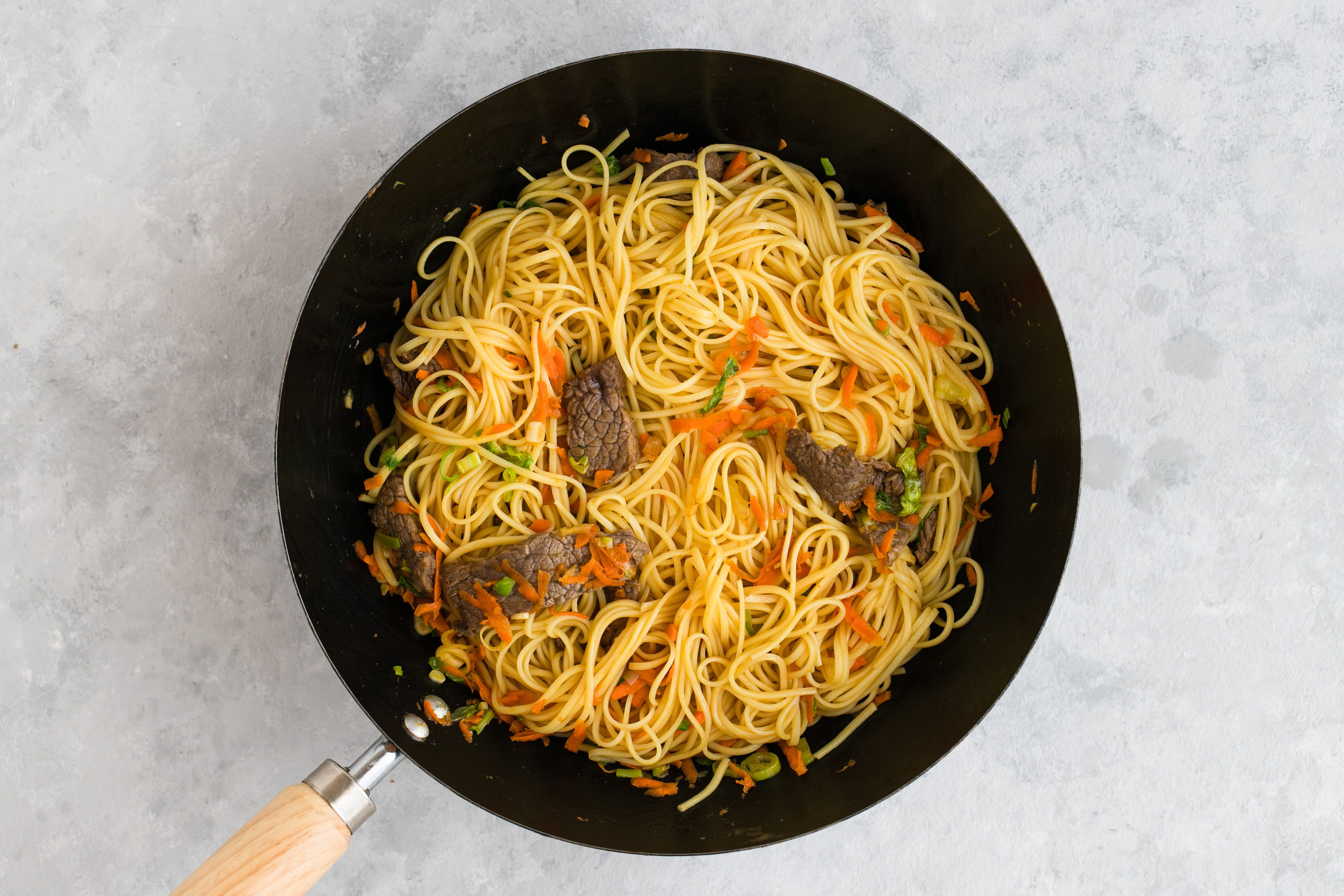 Tossed noodles and beef in wok