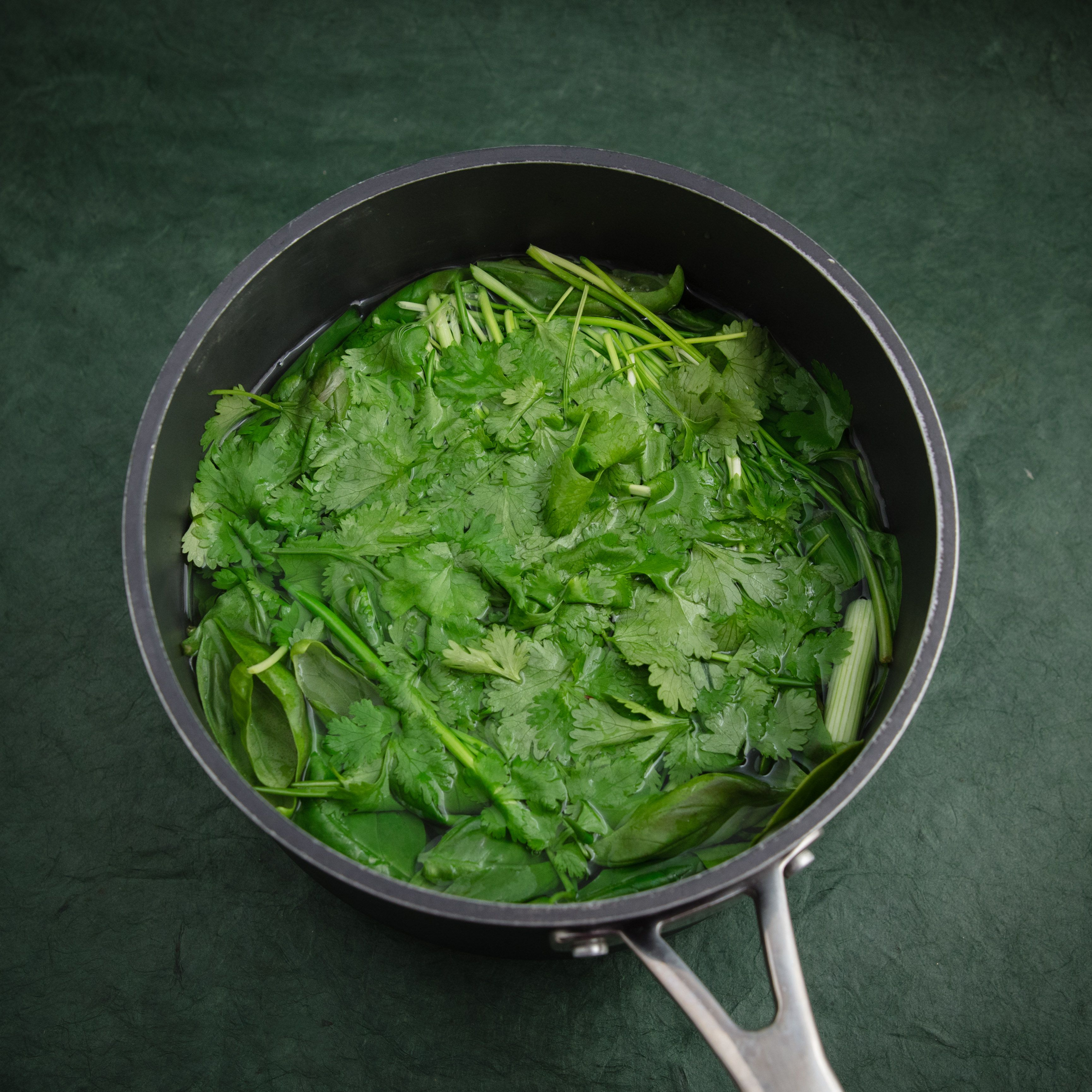 Blanching greens in boiling water.