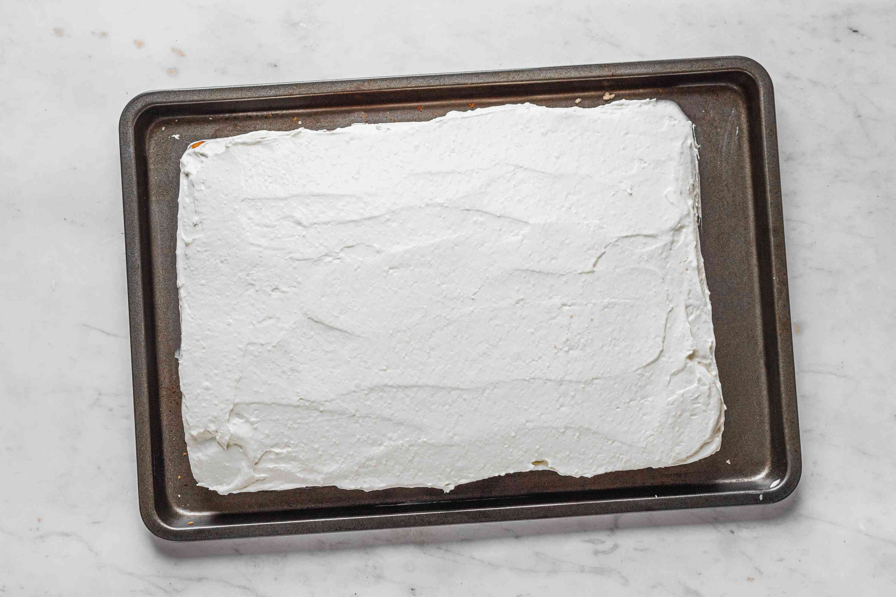 Cake covered with frosting on a baking sheet