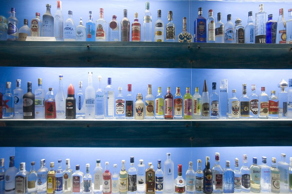 Dozens of bottles of vodka backlit and lined up on shelves