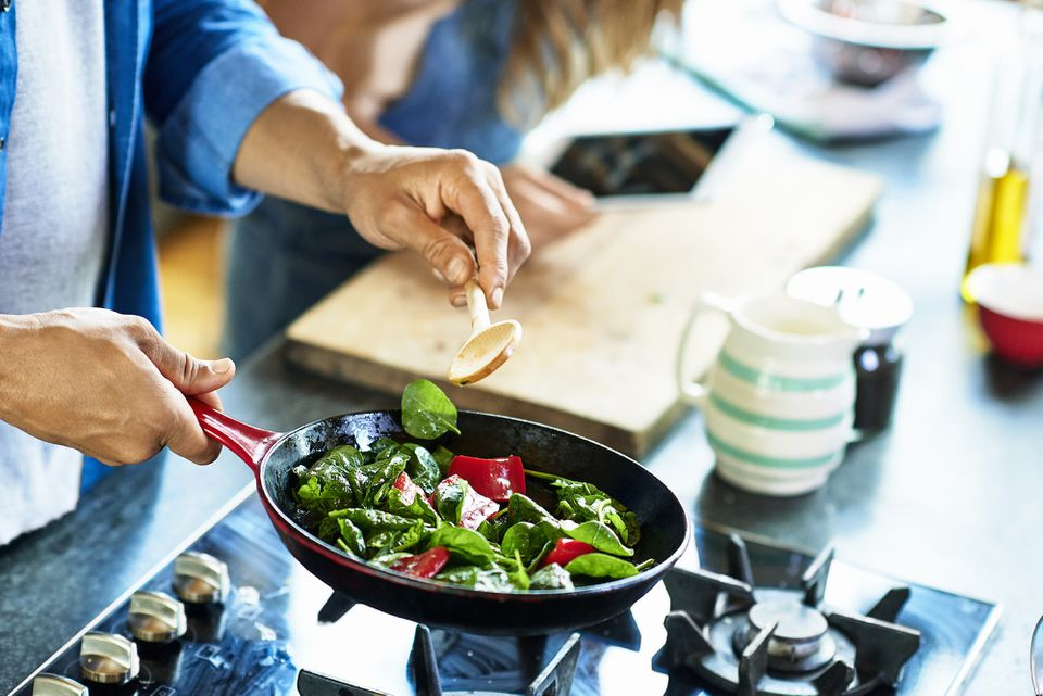 Man tossing vegetables in a frying pan