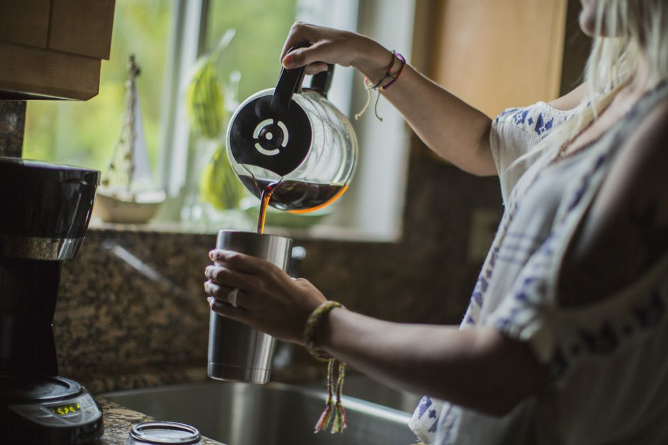Caucasian woman pouring cup of coffee in kitchen