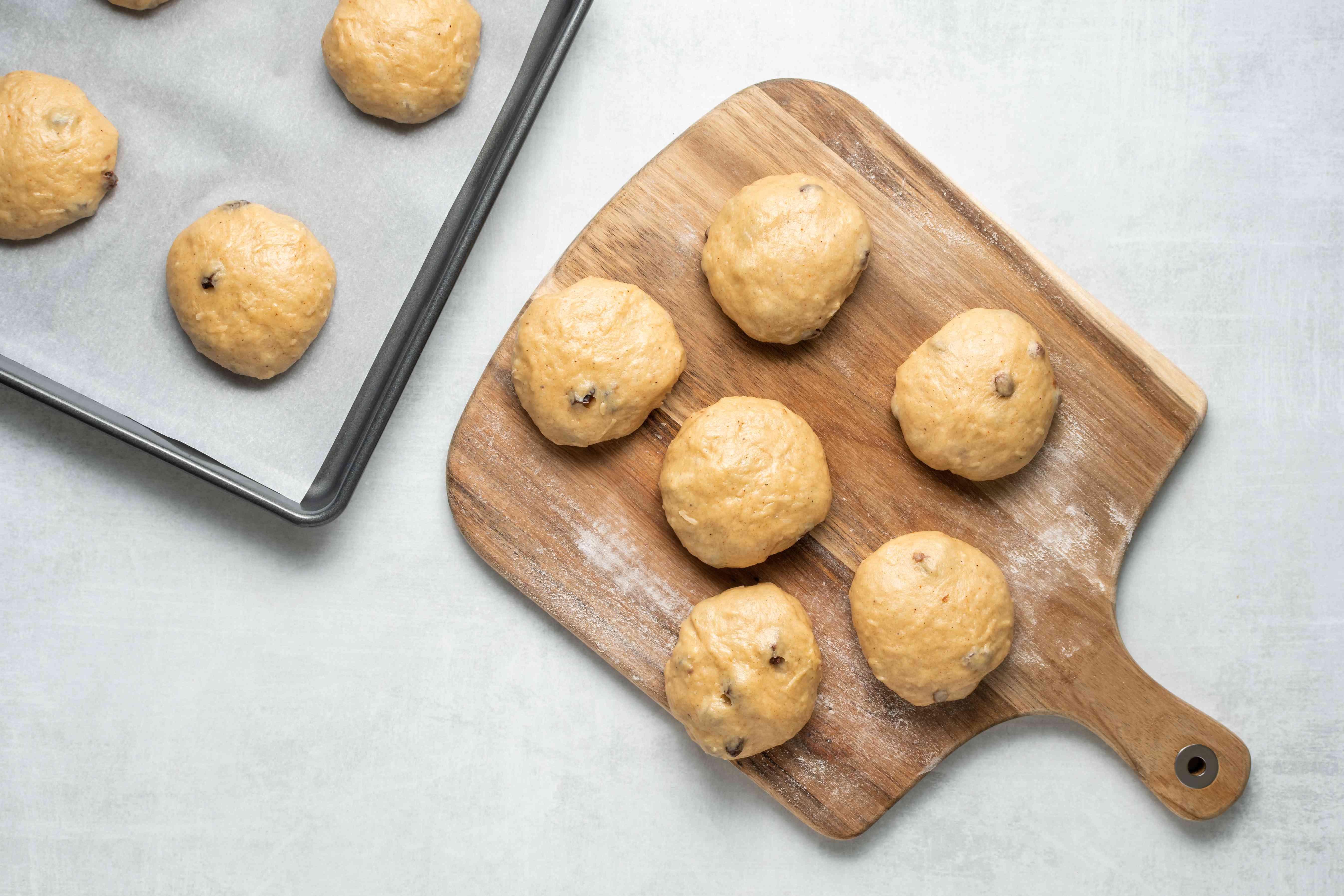 bun dough on a parchment paper lined baking sheet