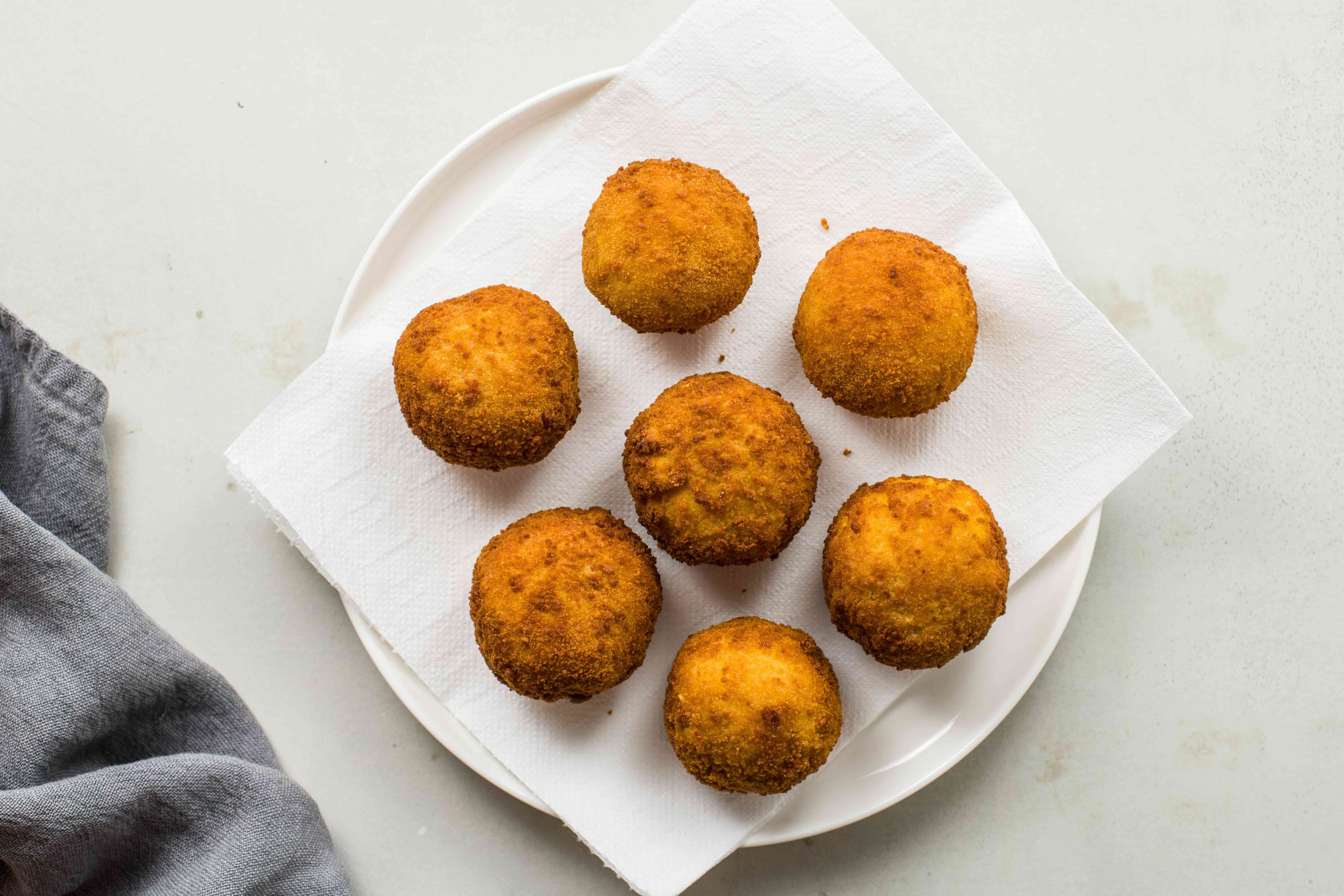 Arancini fried and draining on a paper towel-lined plate