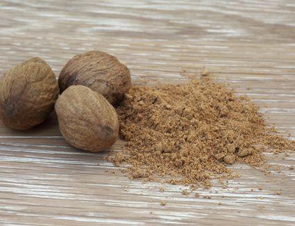 Nutmeg nuts next to ground nutmeg