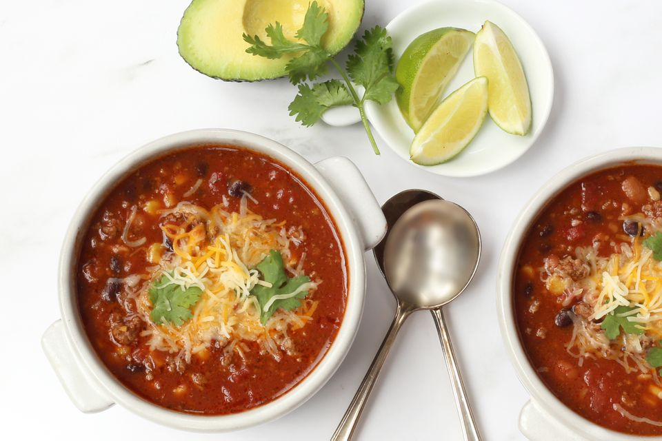 Taco soup in bowls with avocado and lime garnishes