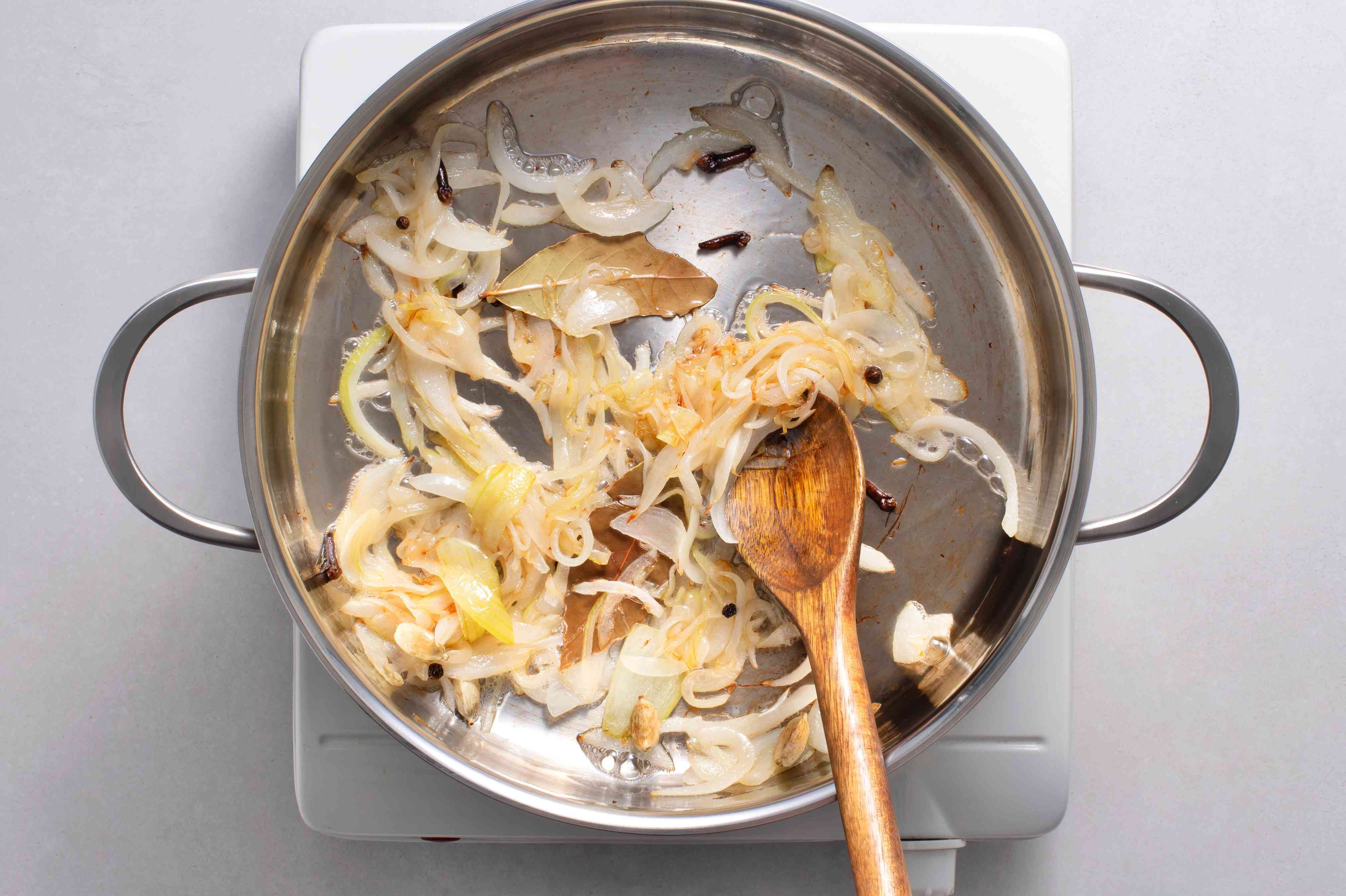 Sliced onions cooking in a pot with bay leaves