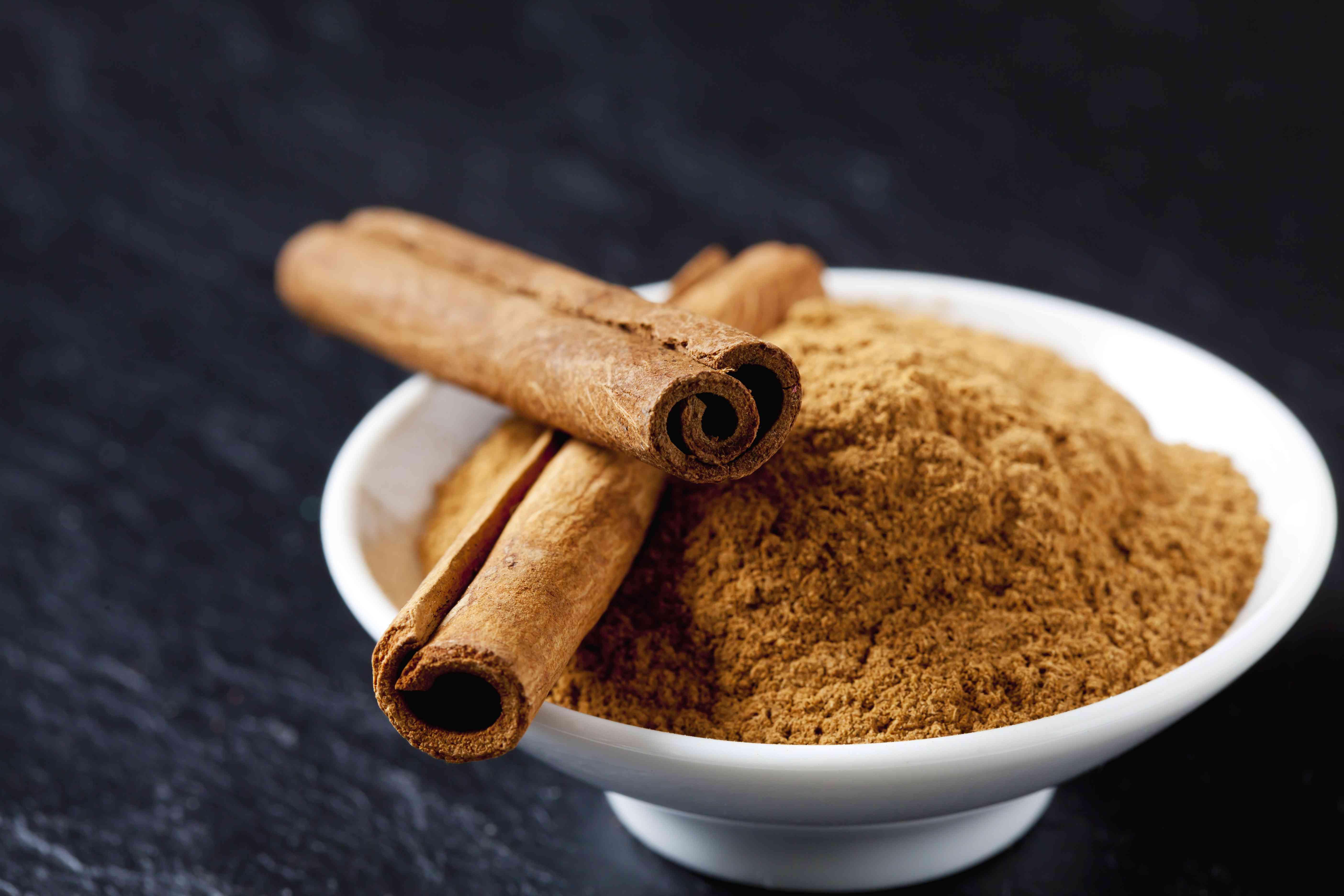 Bowl of cinnamon powder and two cinnamon sticks