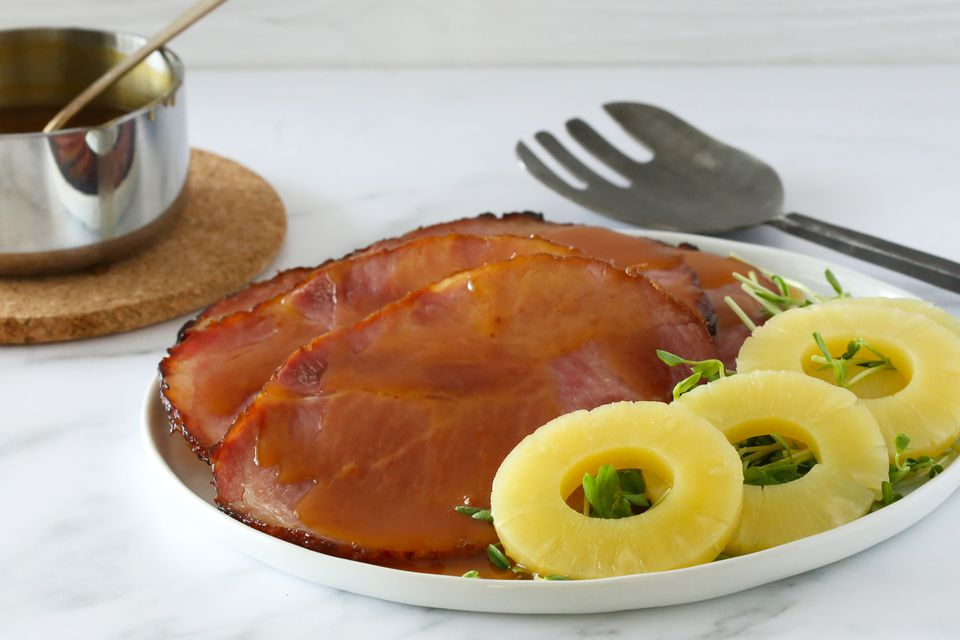 Sliced ham on a platter with pineapple.