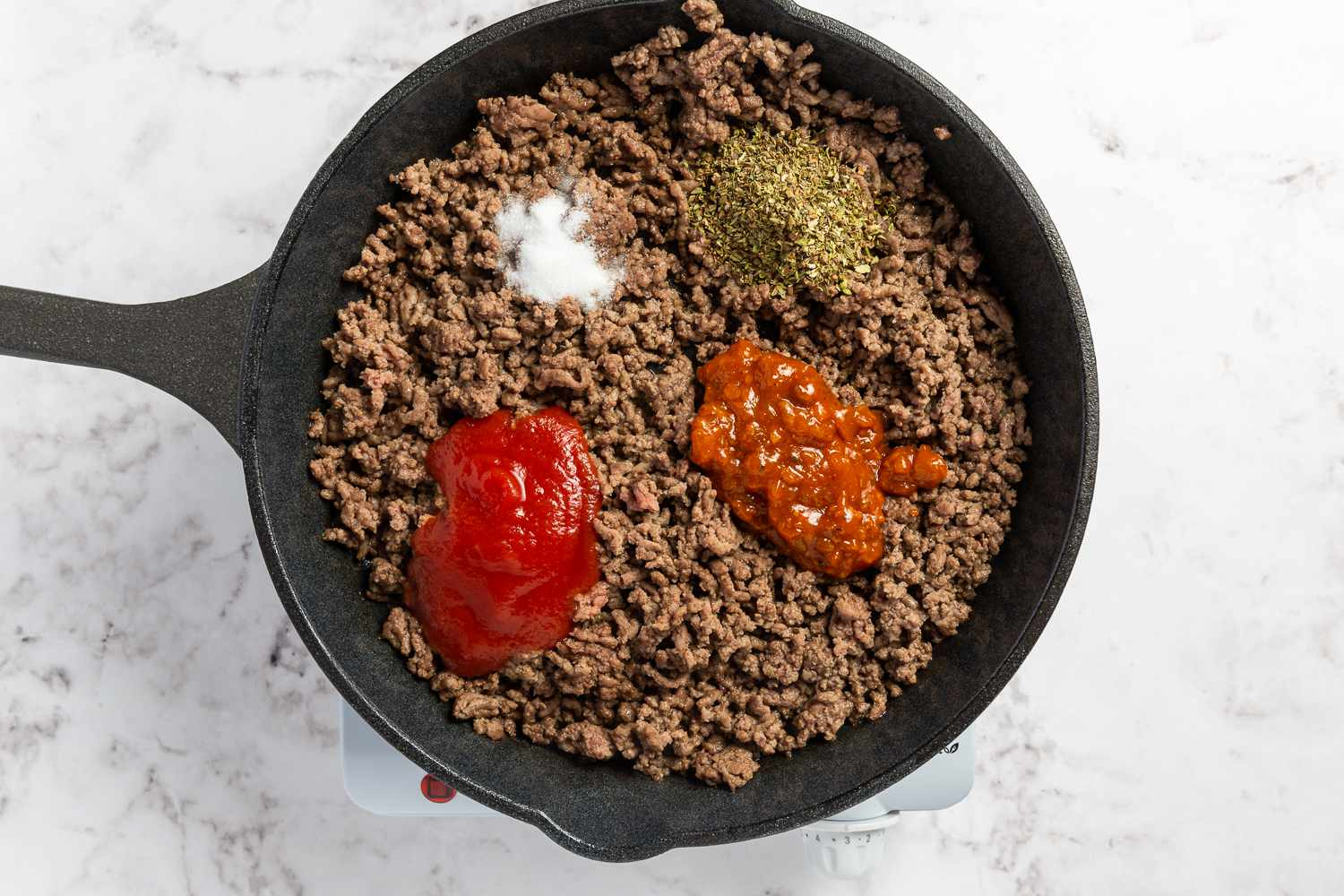 ground beef with seasonings in a frying pan
