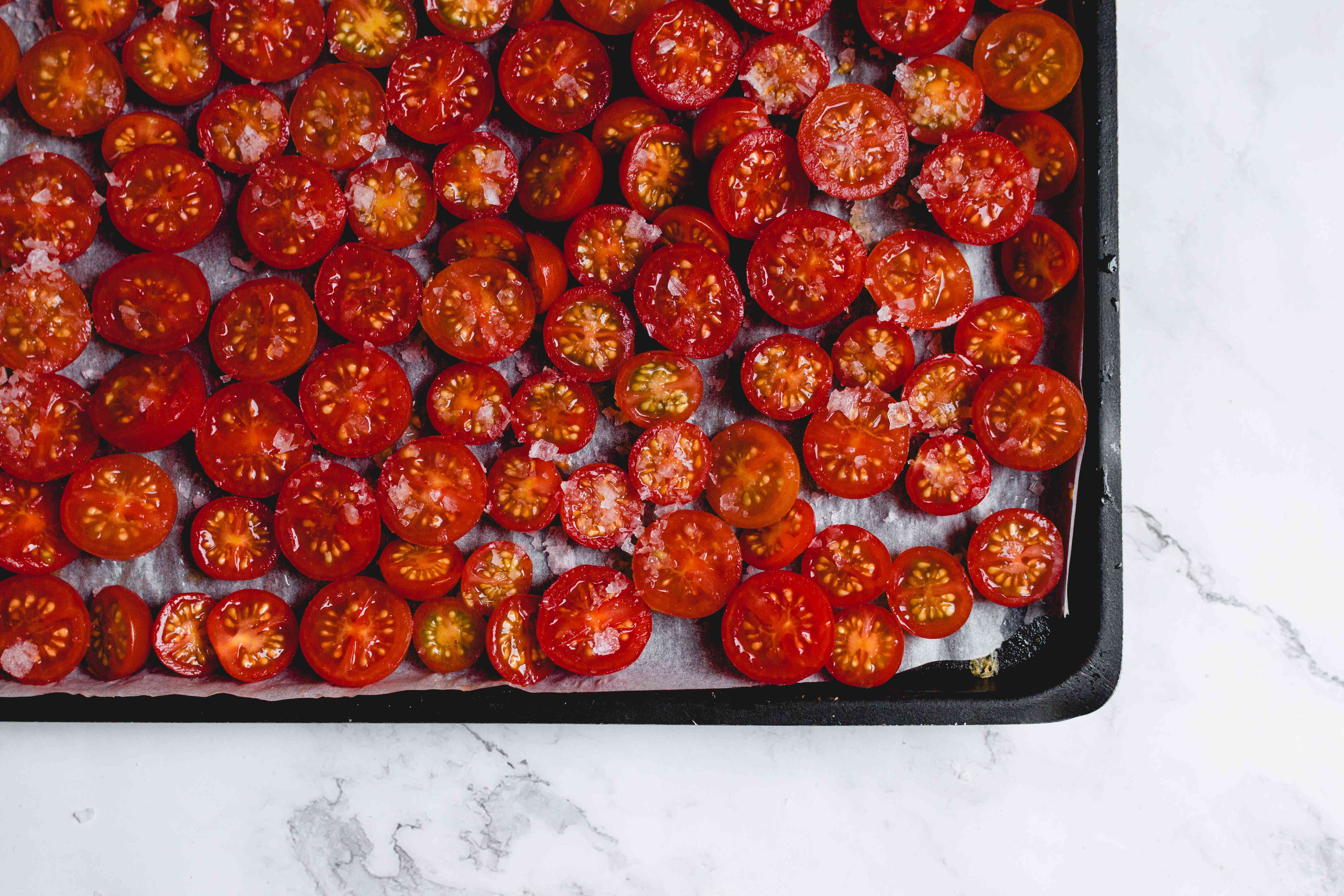 salted tomatoes on a baking sheet