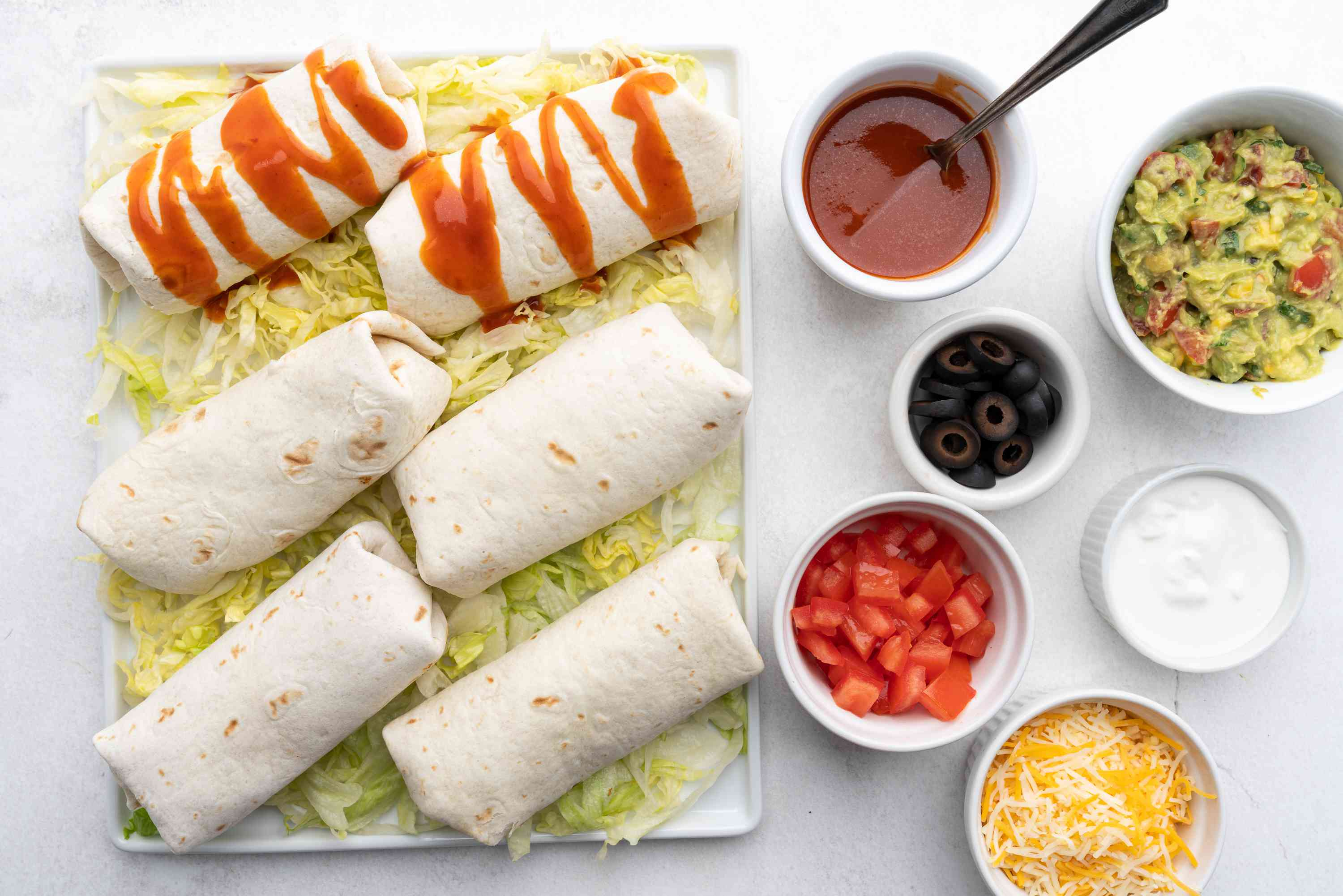 Beef and Bean Burritos on a platter with toppings on the side