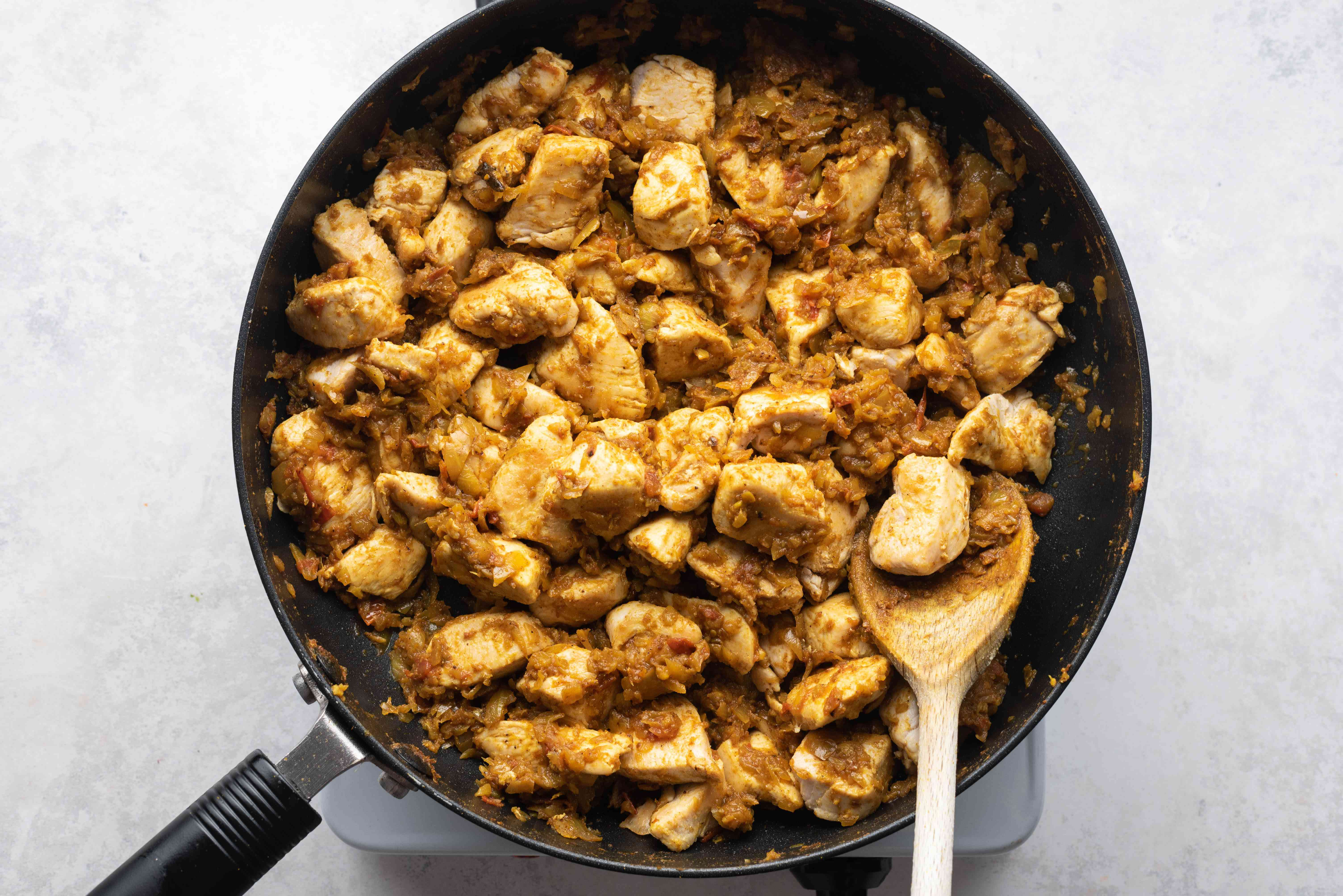 chicken added to the masala mixture in the pan