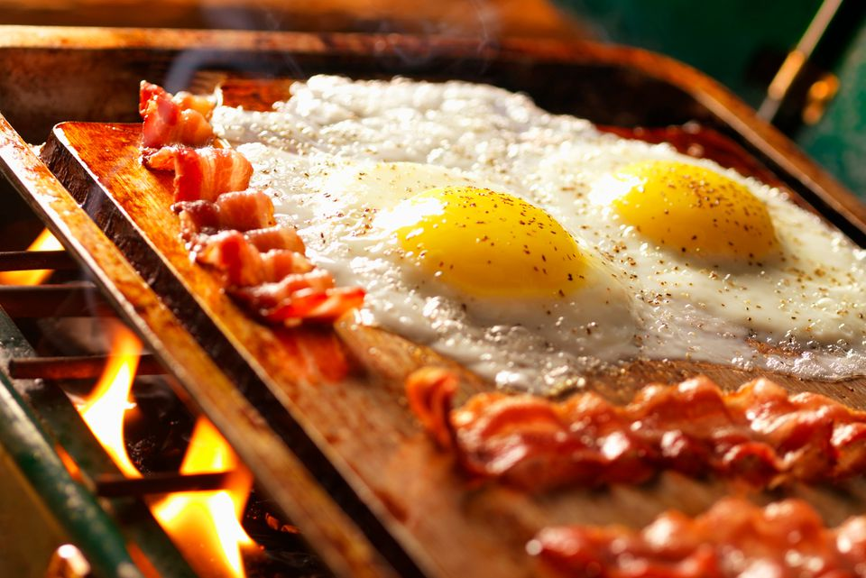 Cooking eggs and bacon on a hot griddle