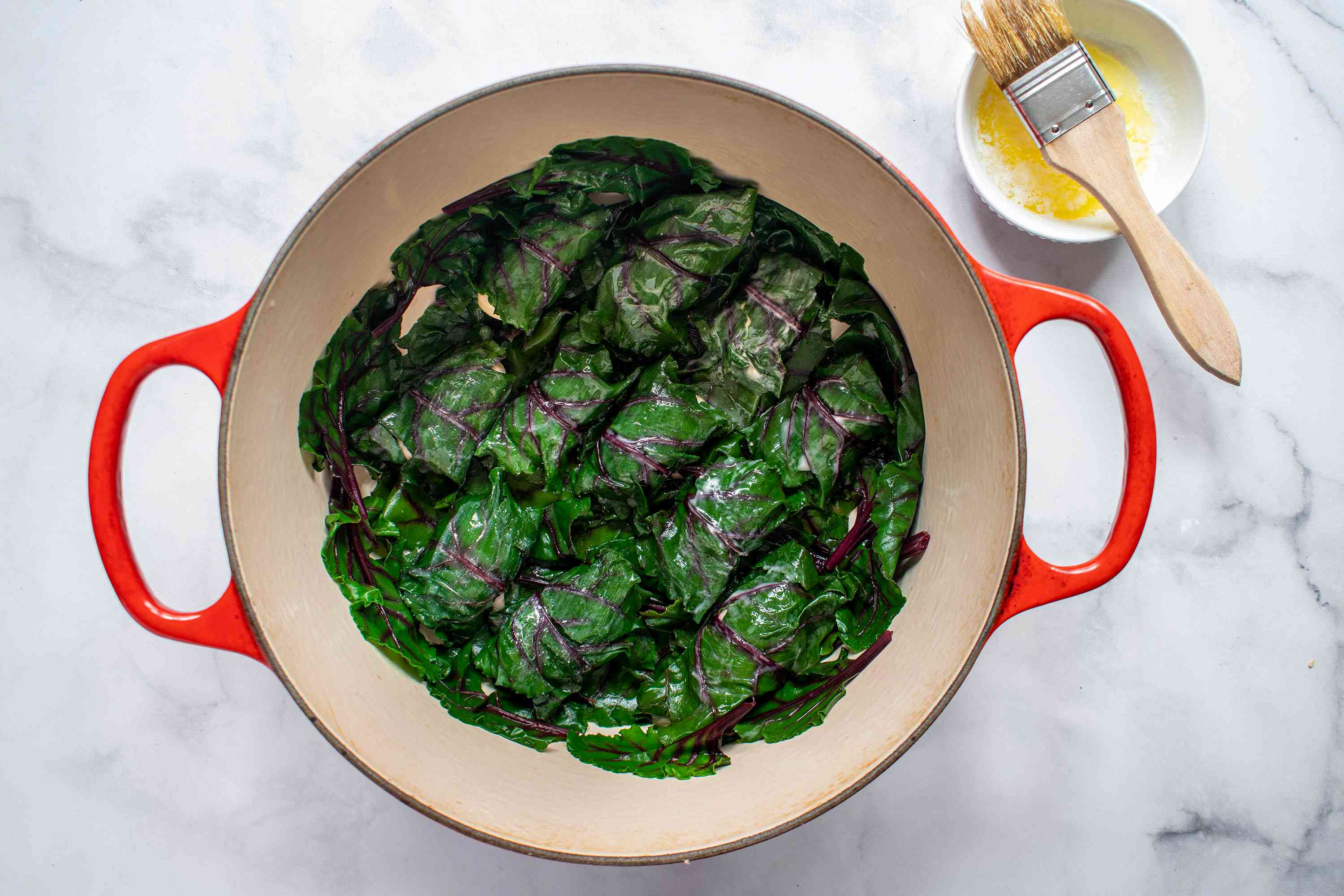 brush the beet leaf rolls with melted butter