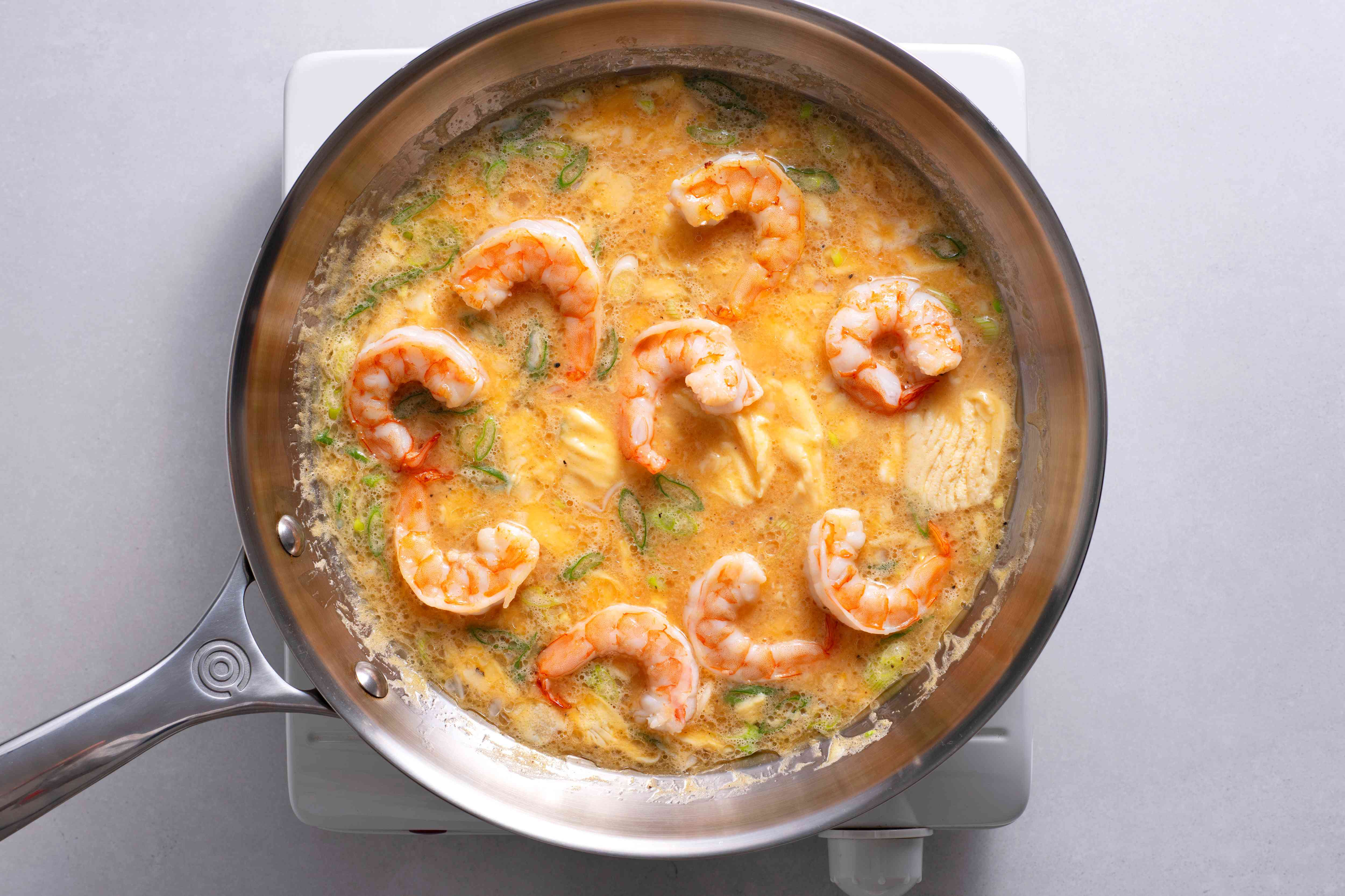 Egg mixture and shrimp cooking in a pan