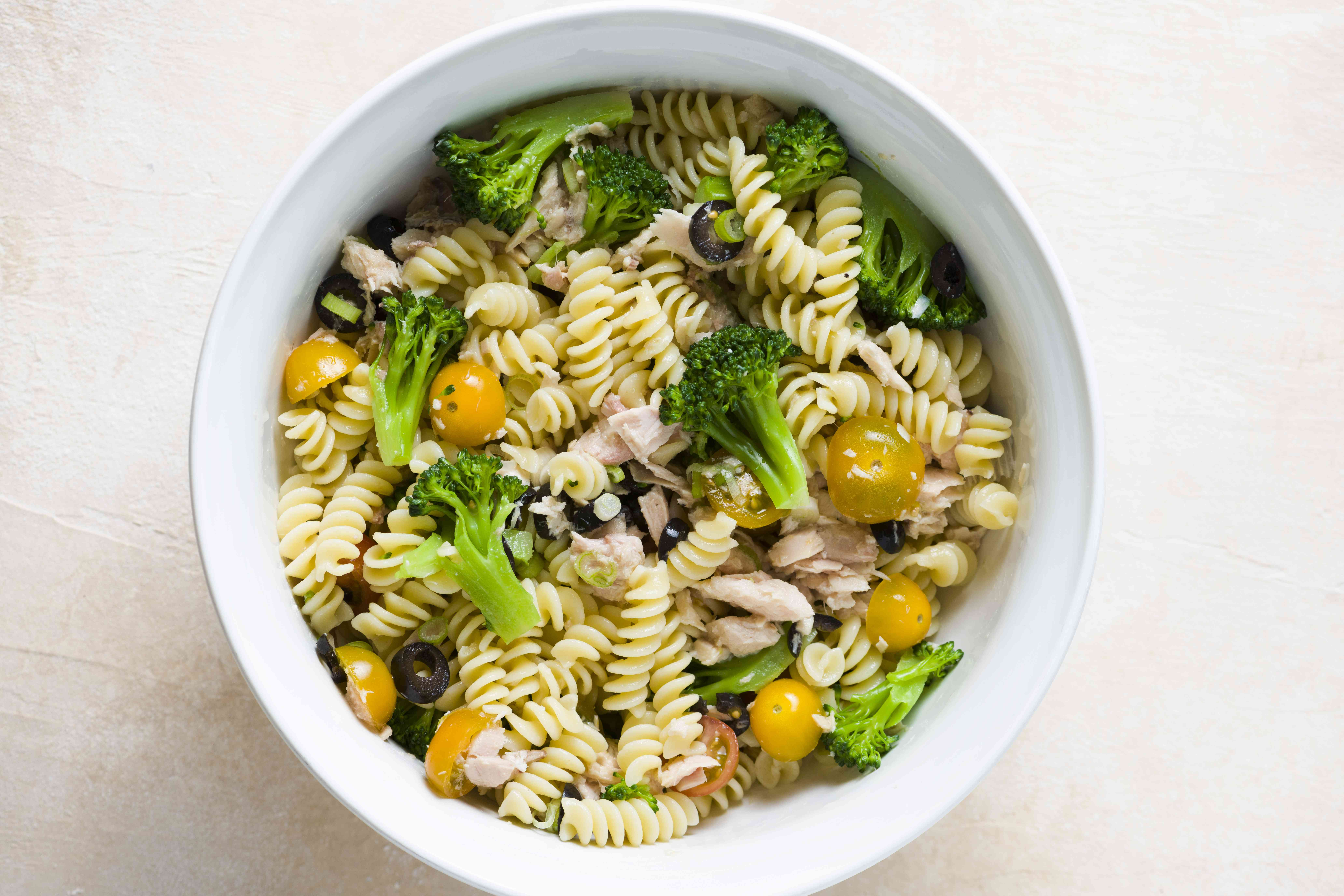 combine the pasta and broccoli with the tuna, tomatoes, olives, and scallions in a bowl